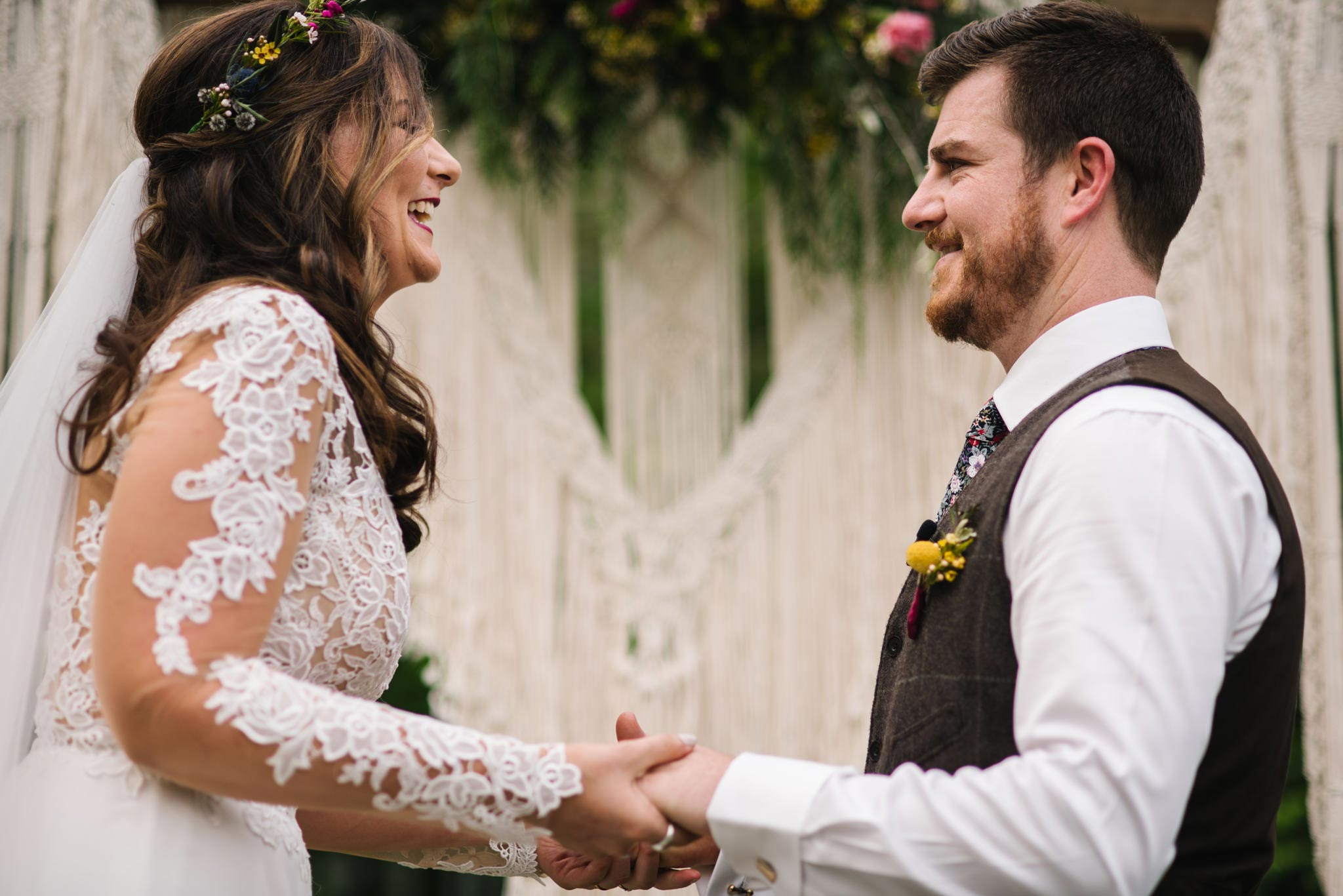Bride and groom smile during ceremony, holding hands