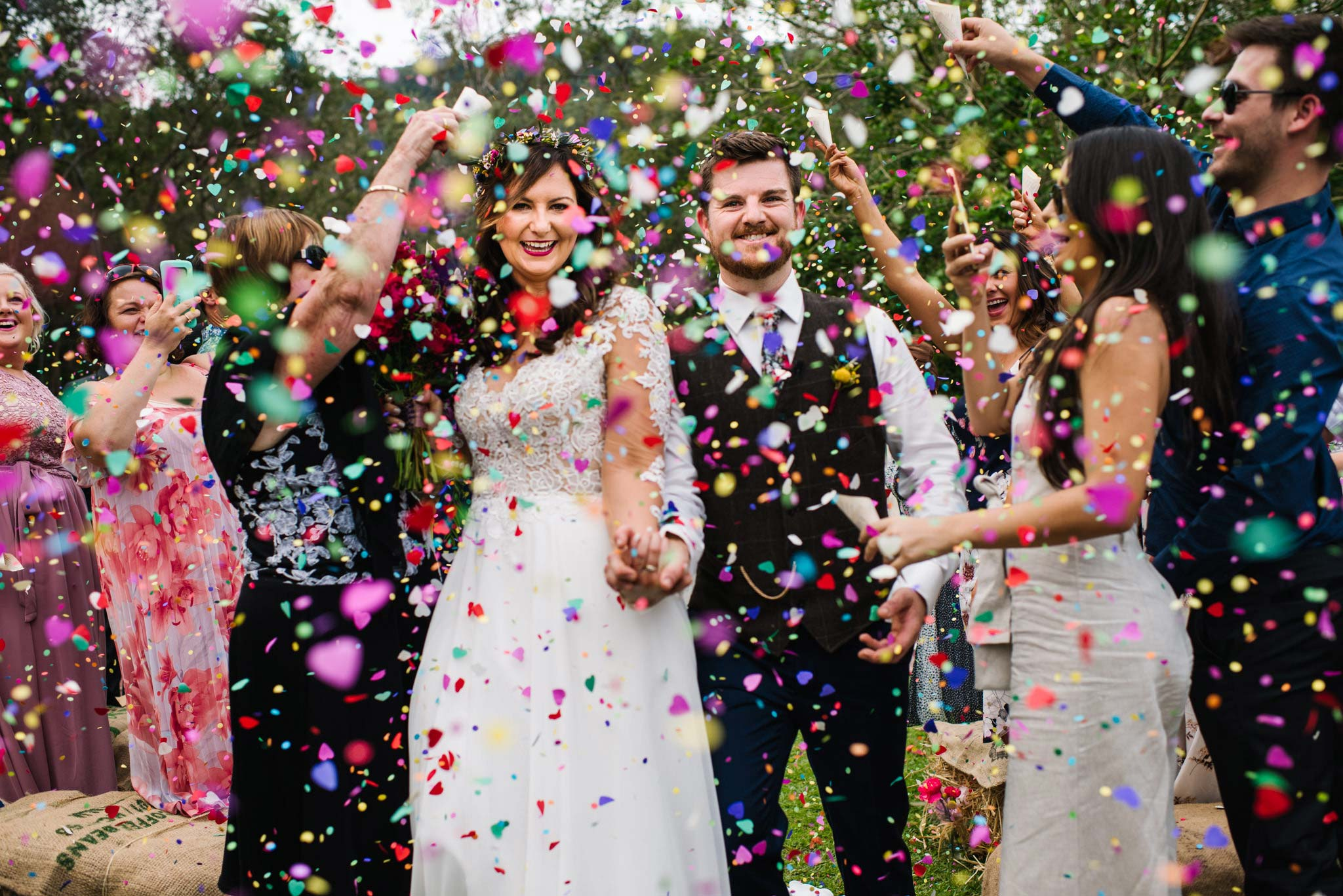 Rainbow confetti showers over smiling bride and groom