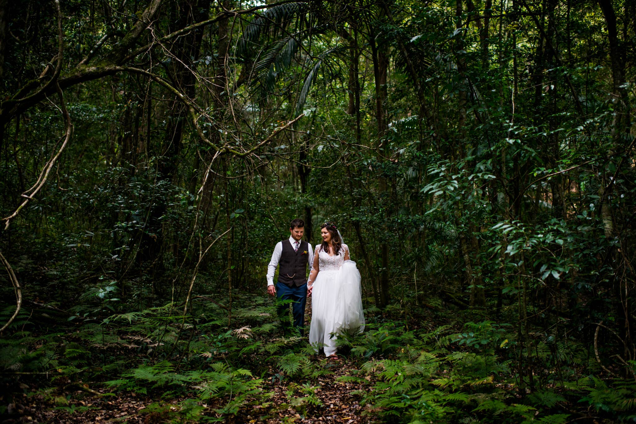 Bride and groom walk through rainforest at country wedding NSW