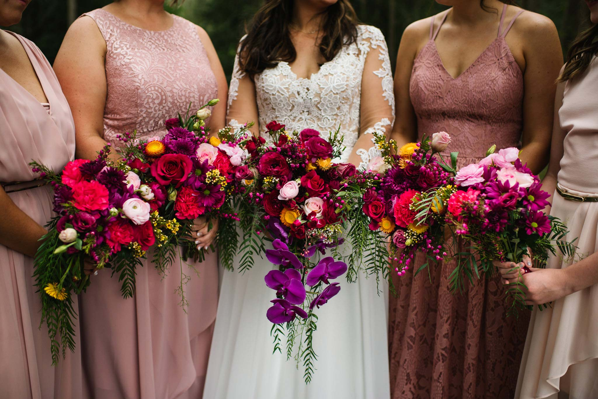 Colourful bouquets held by bride and bridesmaids