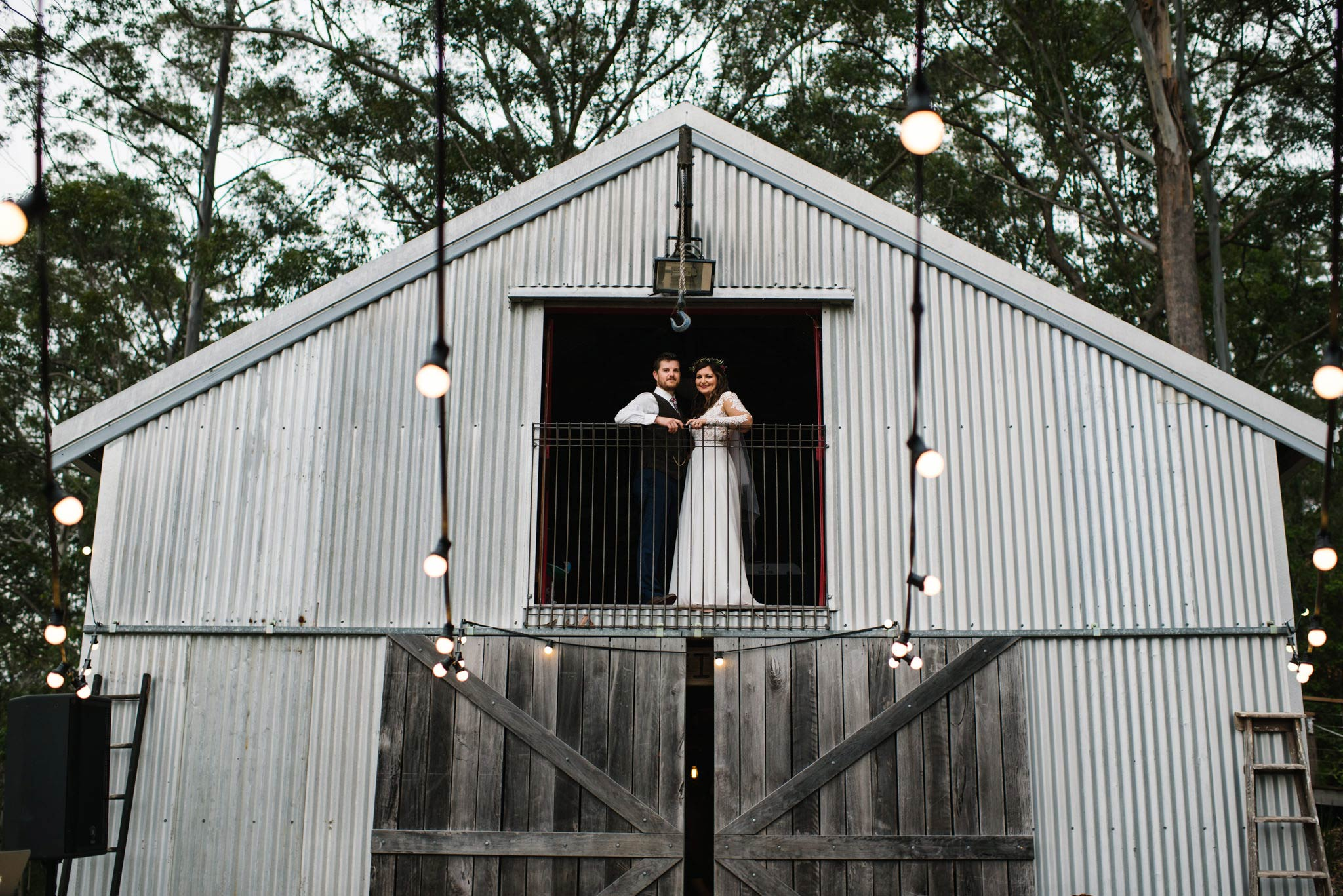 Bride and groom posing in the upper window of a barn