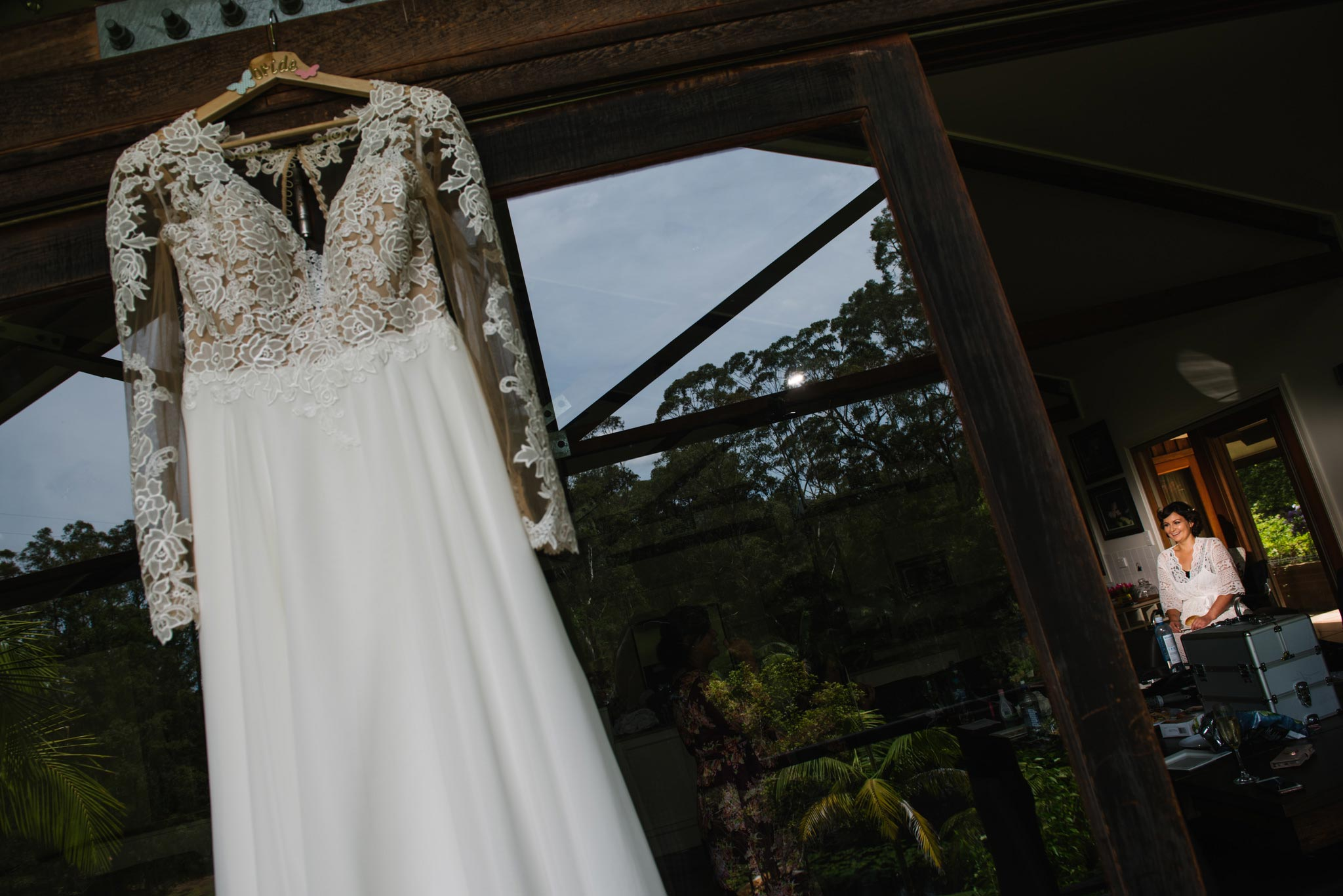 Vintage dress hanging with bride getting ready in the background