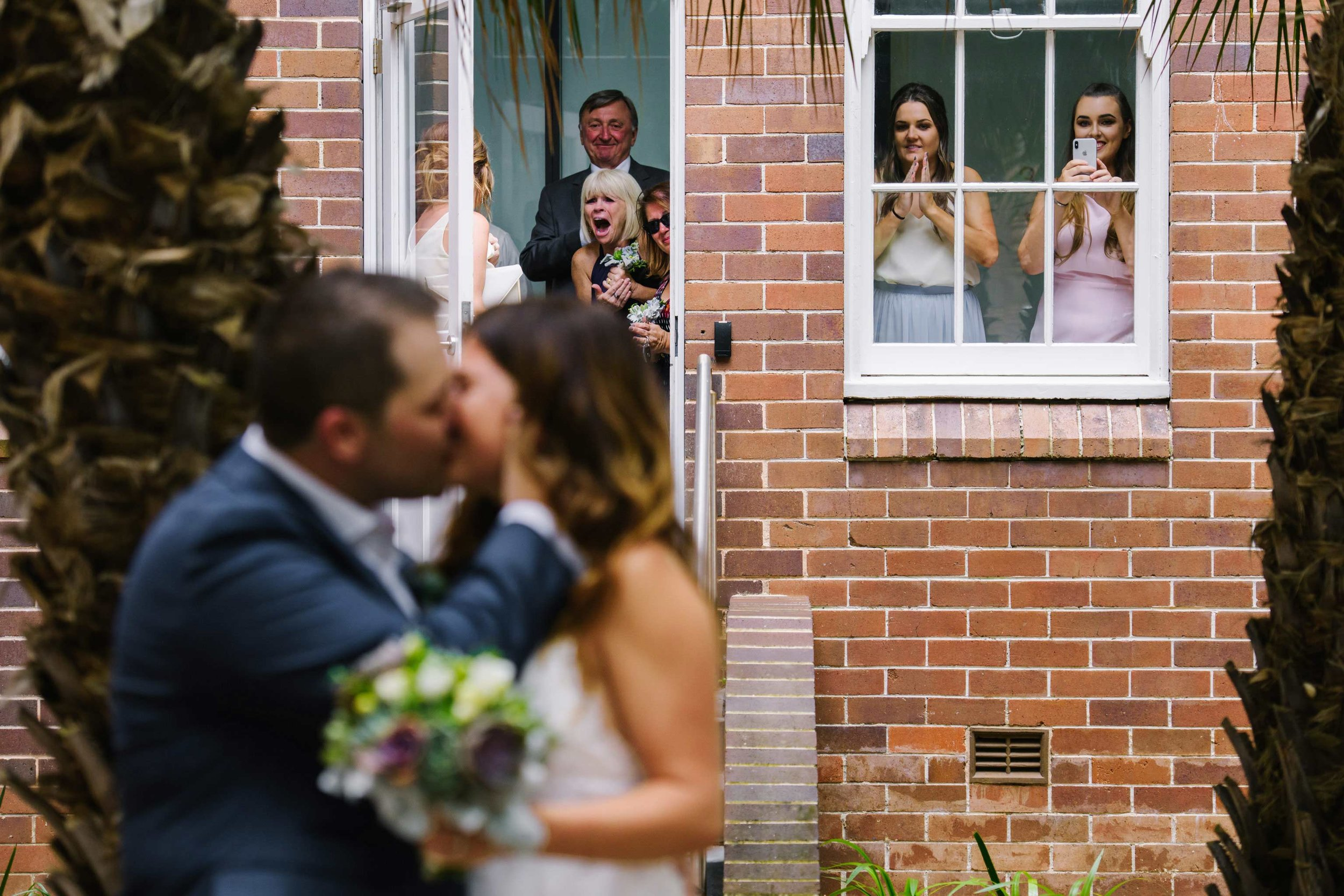 Bride and groom kiss after first look while family looks on