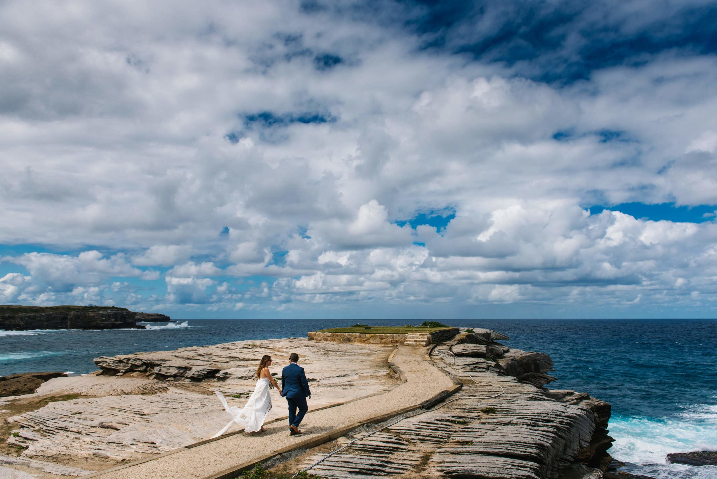 Bride and groom walking along outlook at Little Bay, NSW