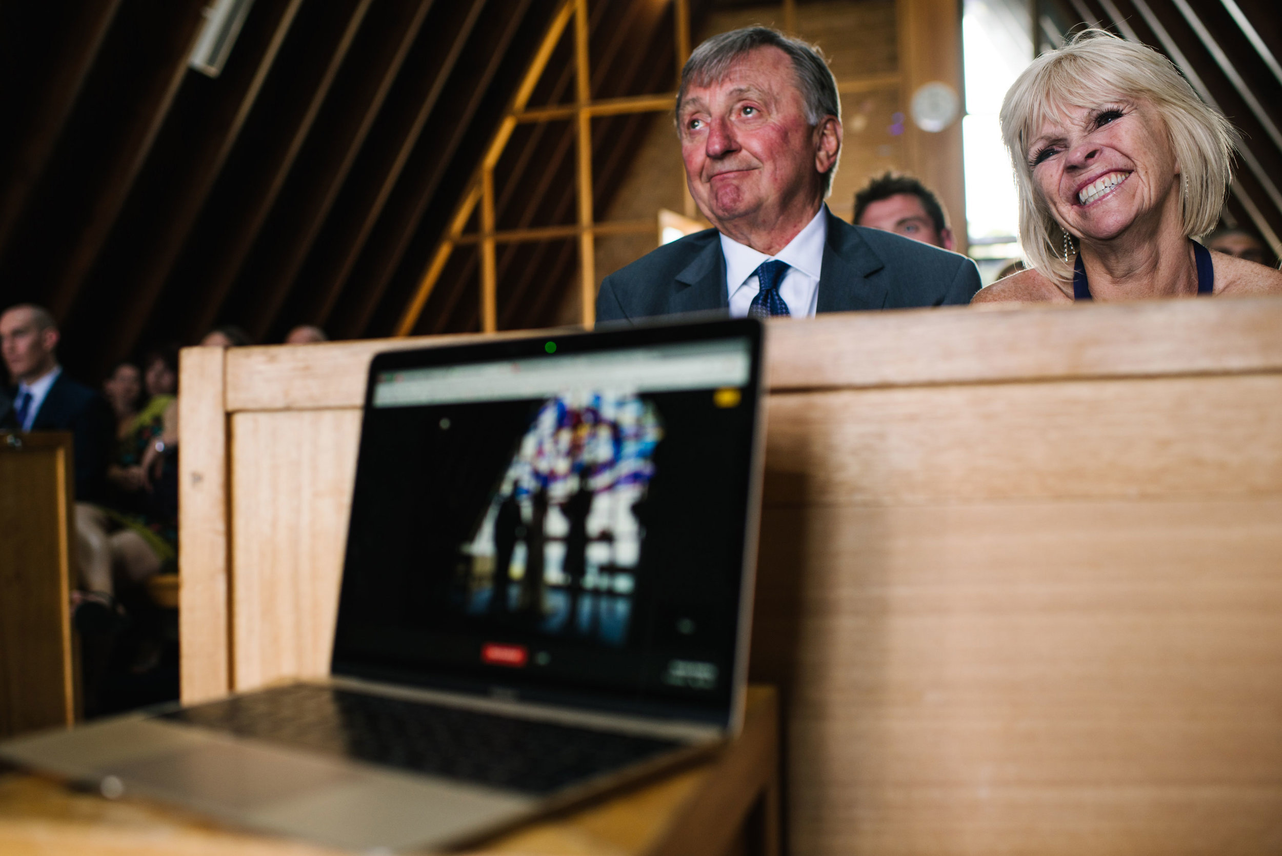 Parents of the bride smile as they watch wedding ceremony