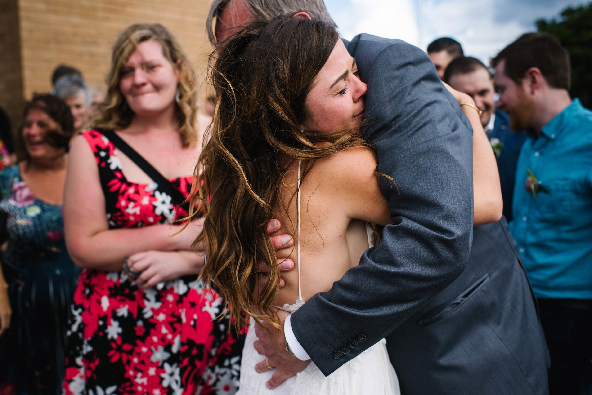 Bride hugs father after wedding service