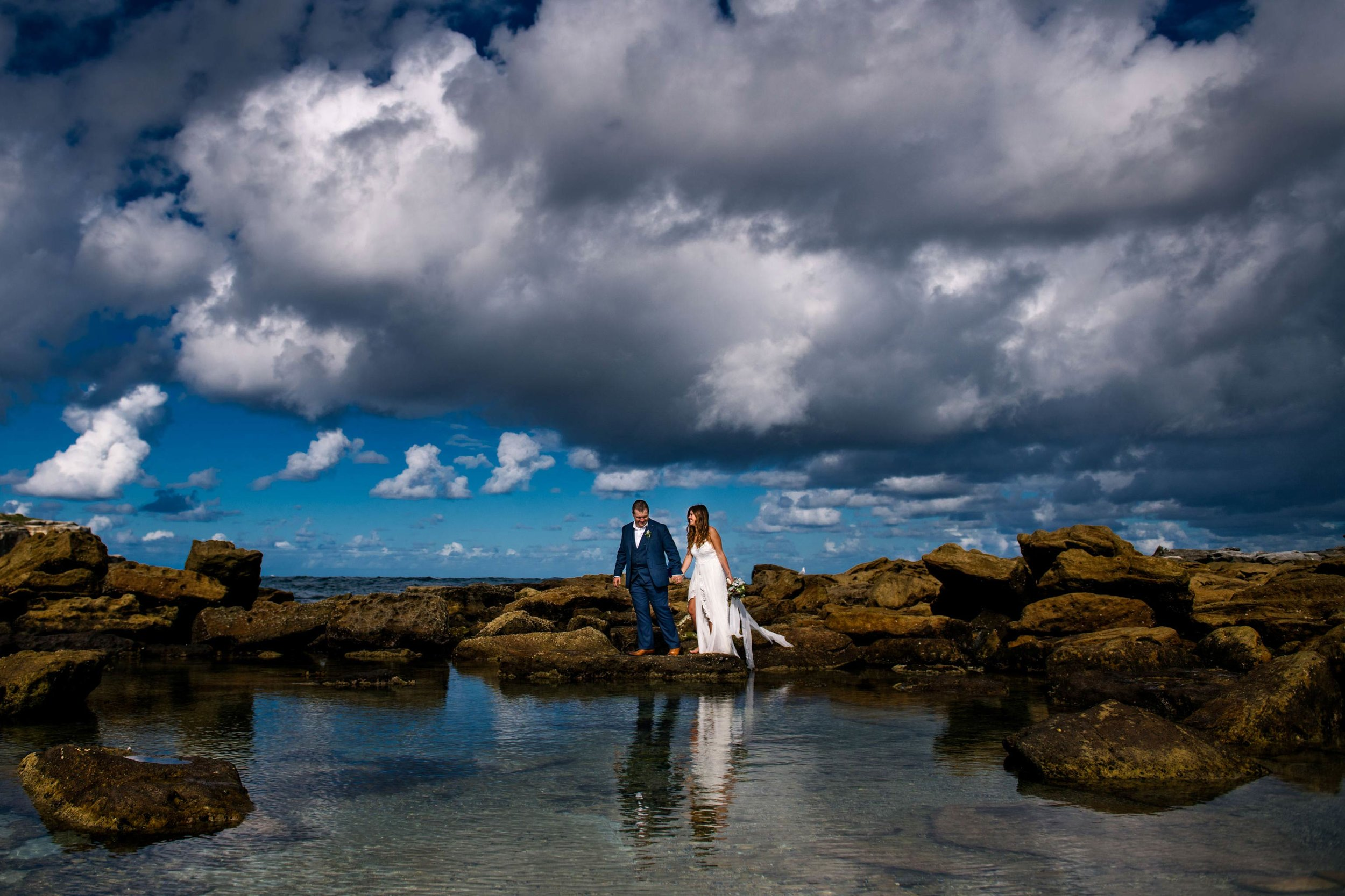 Newlyweds amongst rocks and shoreline at Little Bay
