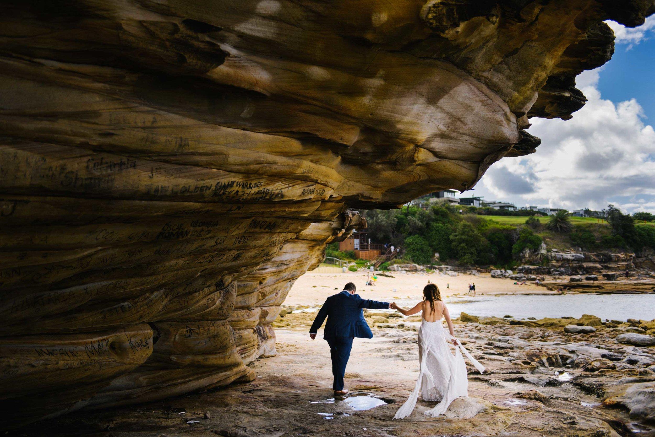 Newlyweds walk under rock outcrop along the beach