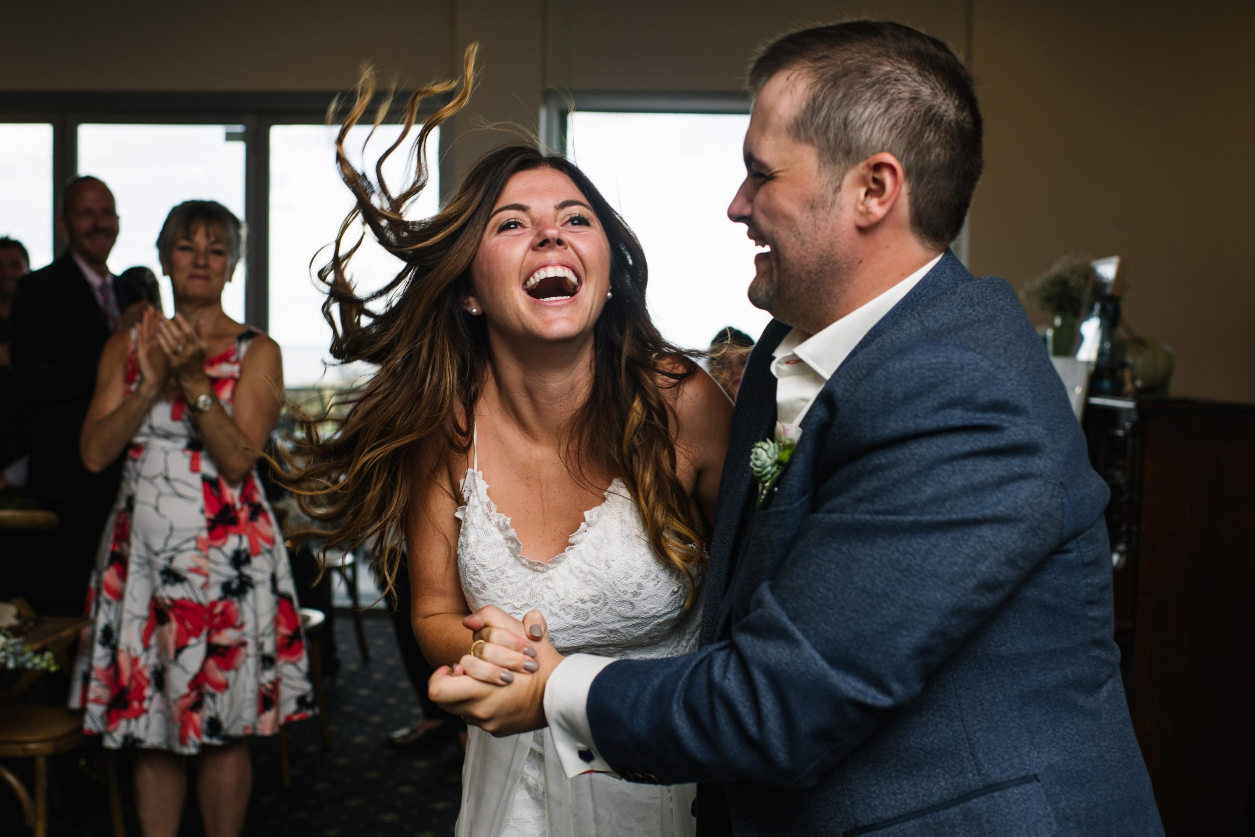 Bride laughing during entrance to wedding reception