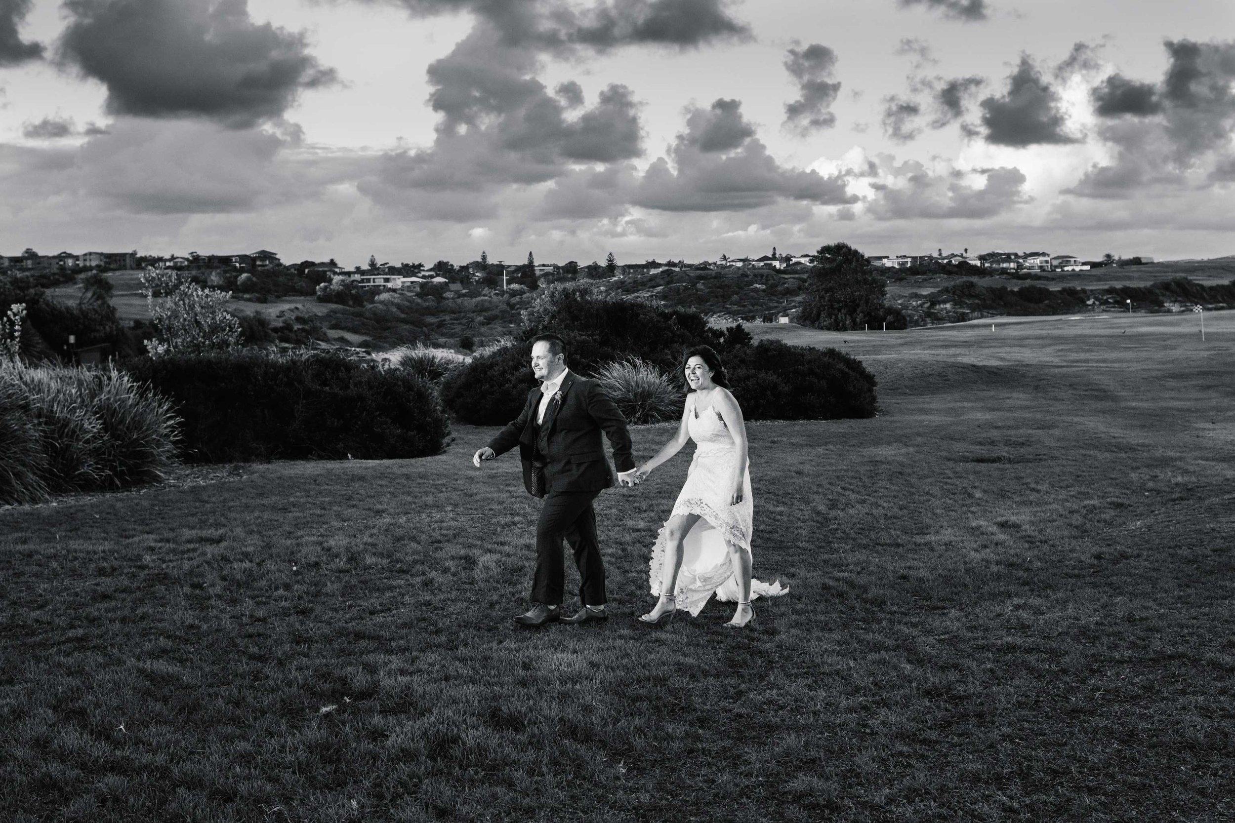 Bride and groom walking across lawn at Coast Golf Club Little Bay