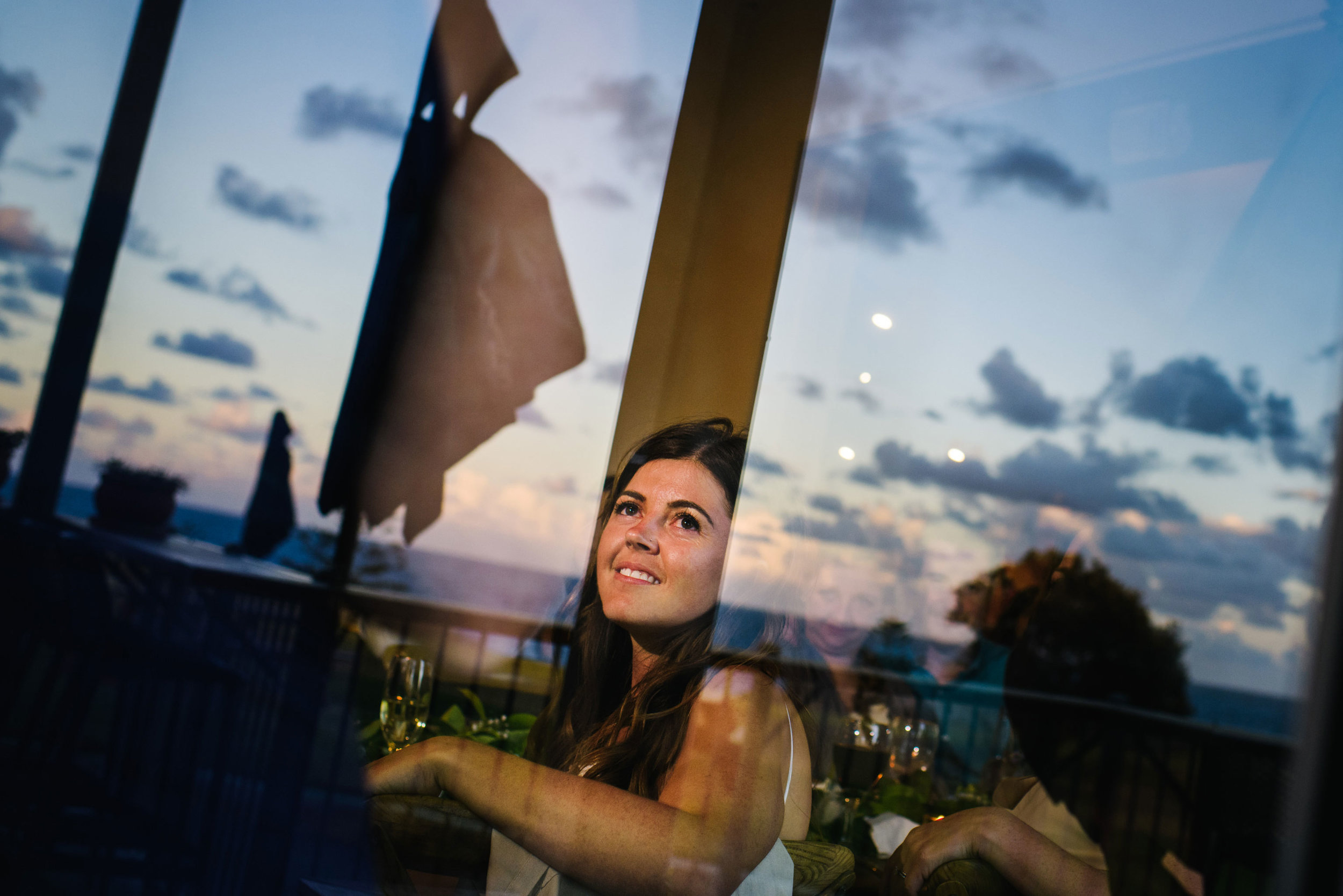 Bride smiling with the evening sky reflected in windows
