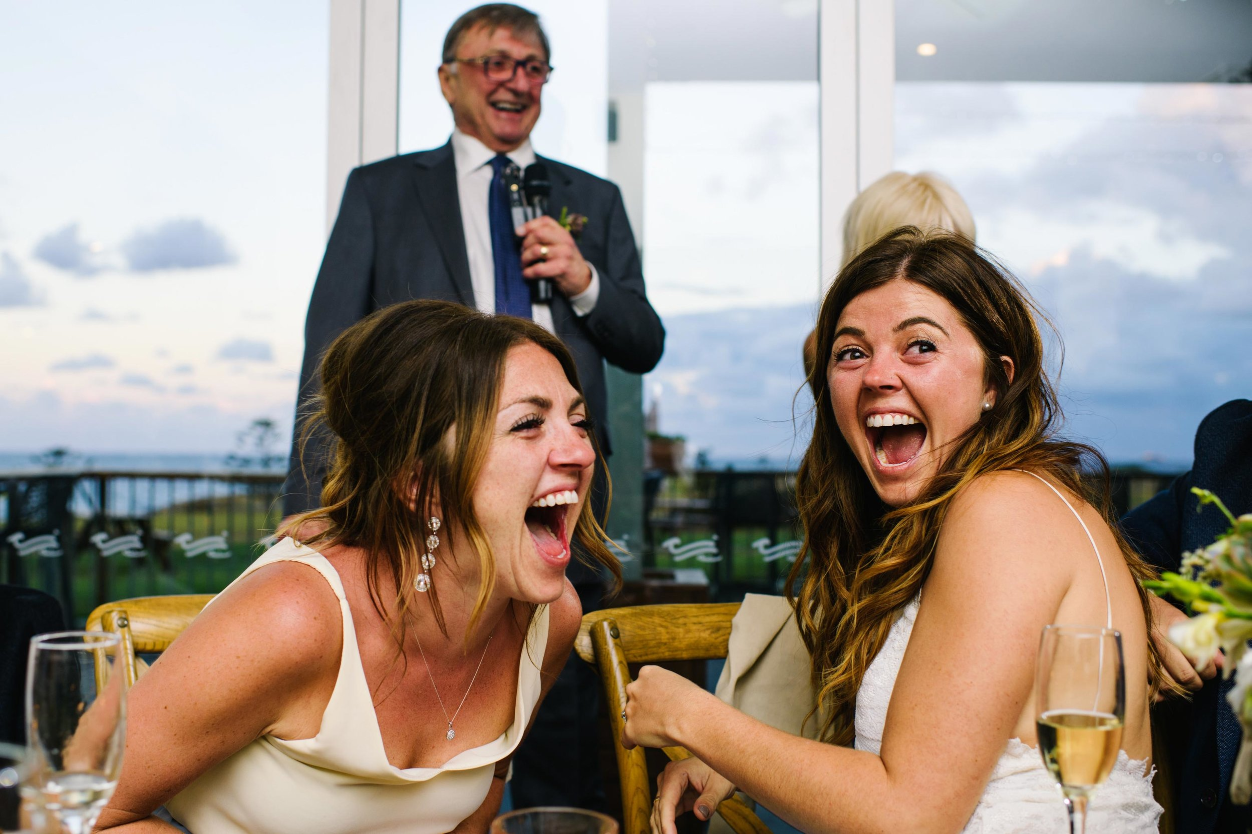 Bride and sister laughing at Coast Golf Club reception