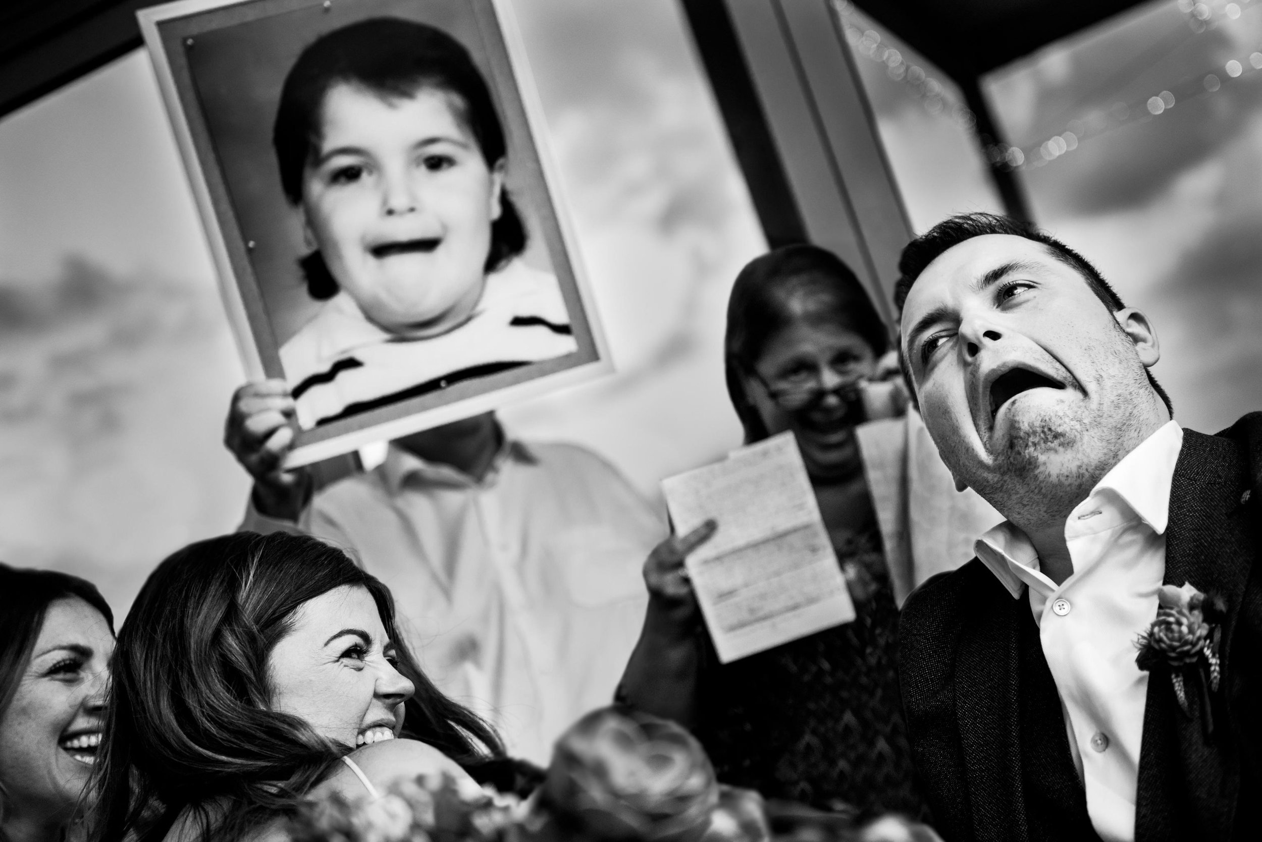 Groom making hilarious face trying to replicate a school photo of himself during father's speech