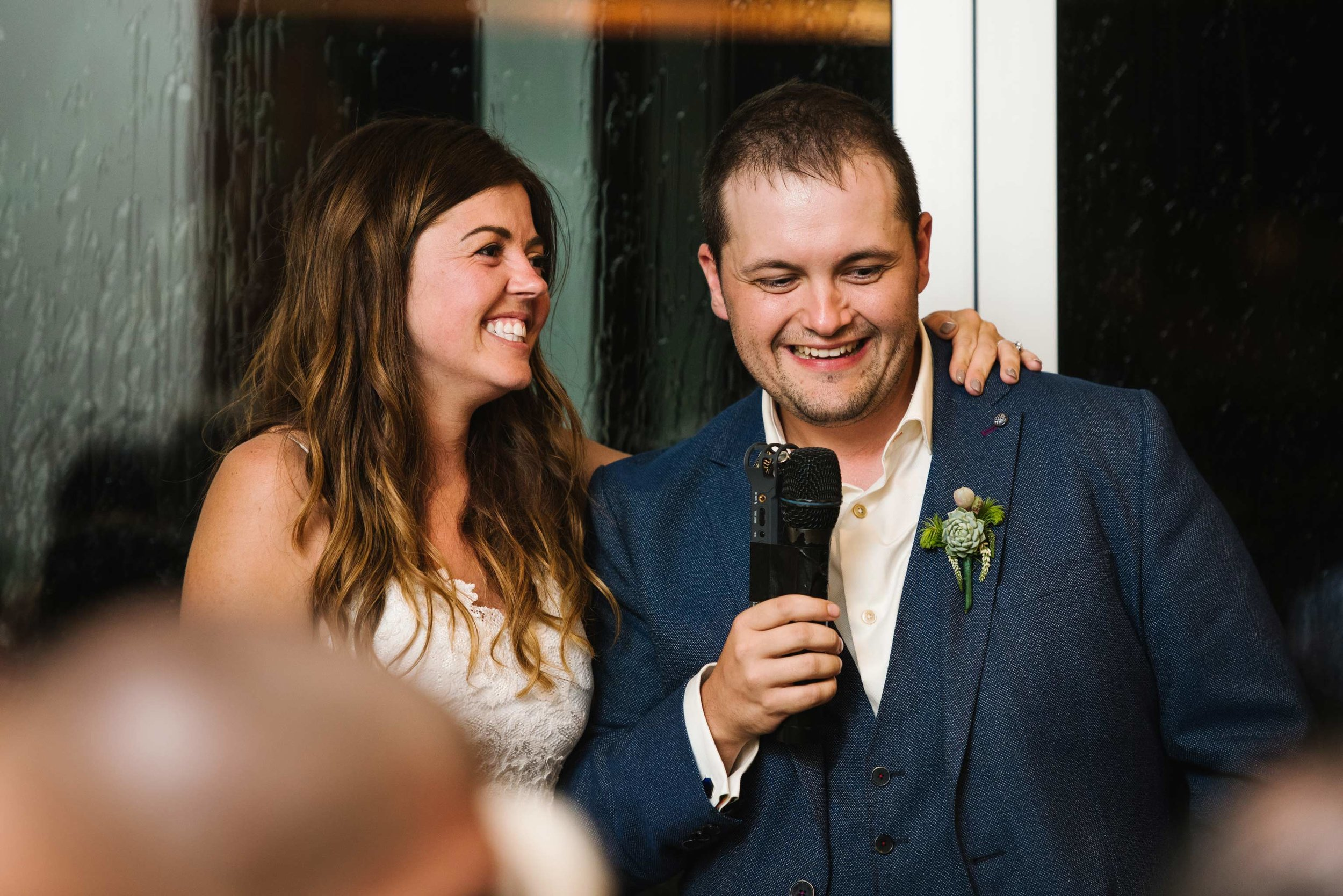 Newlyweds laughing during speeches