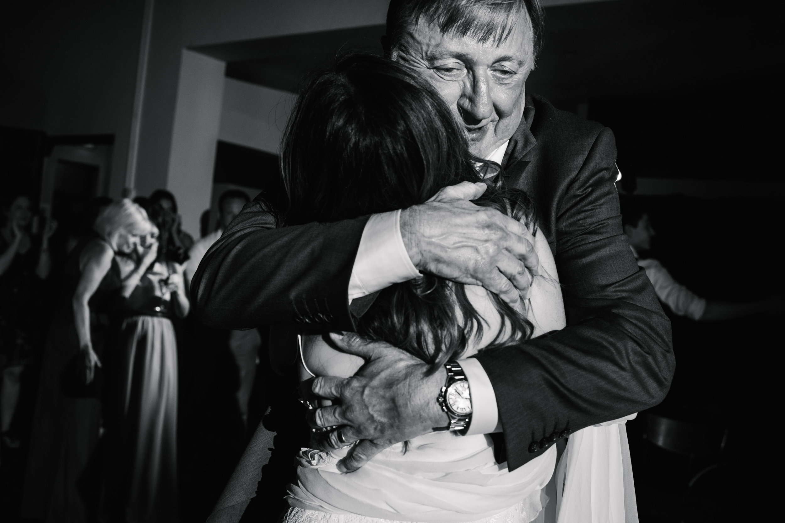 Father hugging daughter and looking emotional during dance