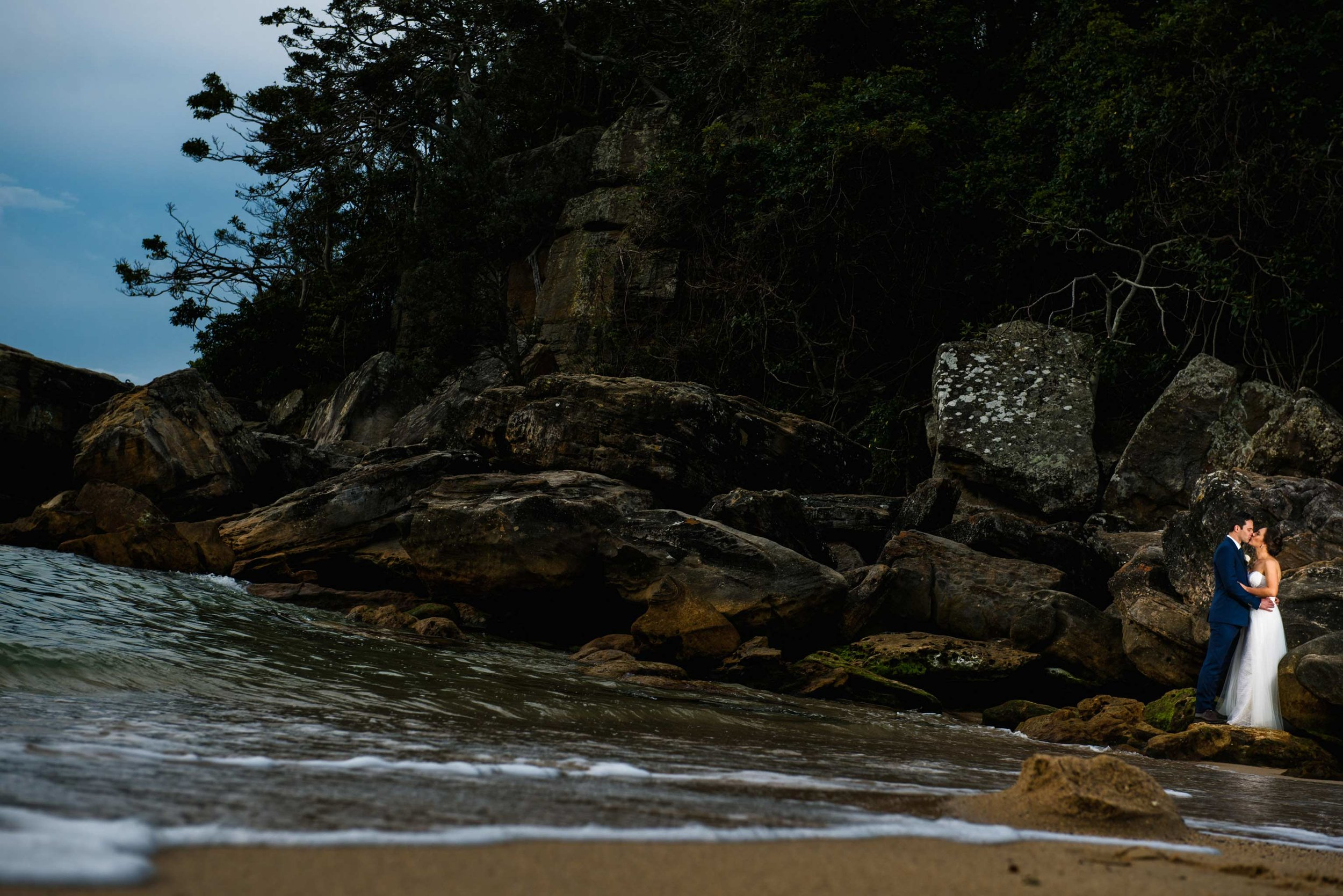Bride and groom on rocks at Shelly Beach