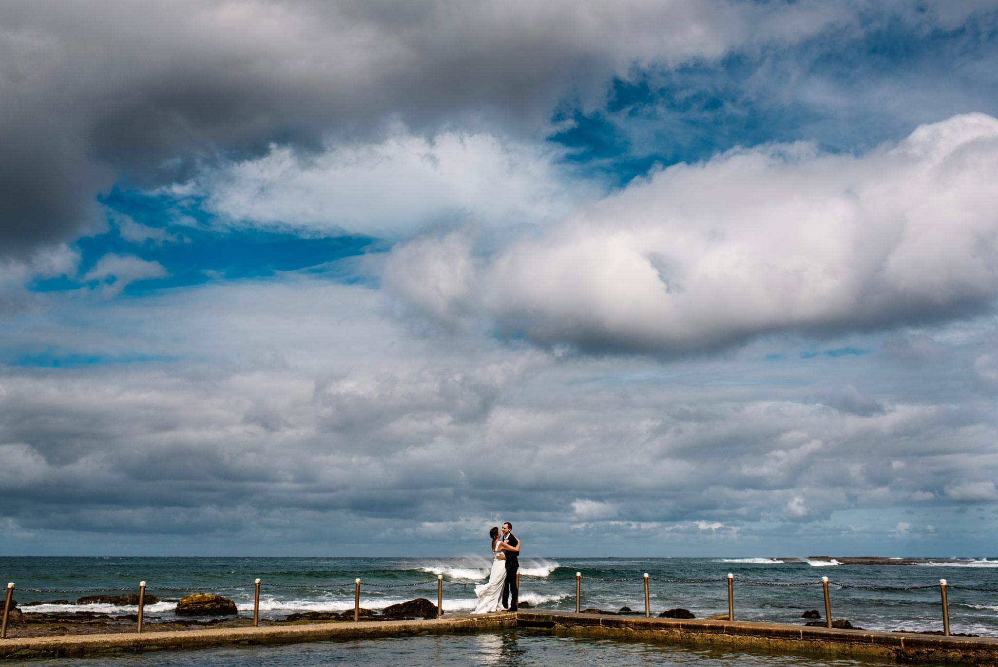 Newlyweds under expansive sky at Mona Vale beach