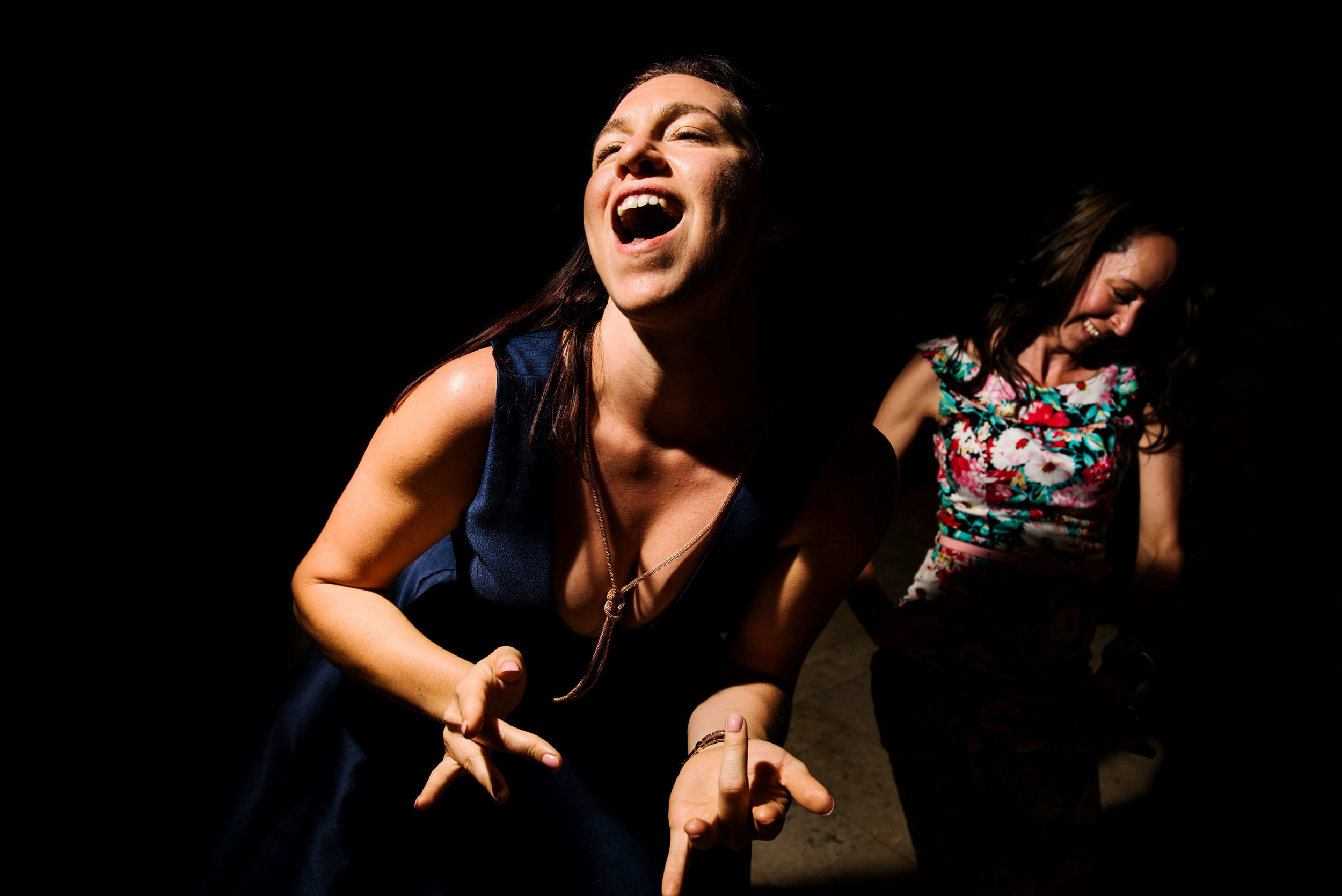 Woman laughing and playing air guitar at wedding reception