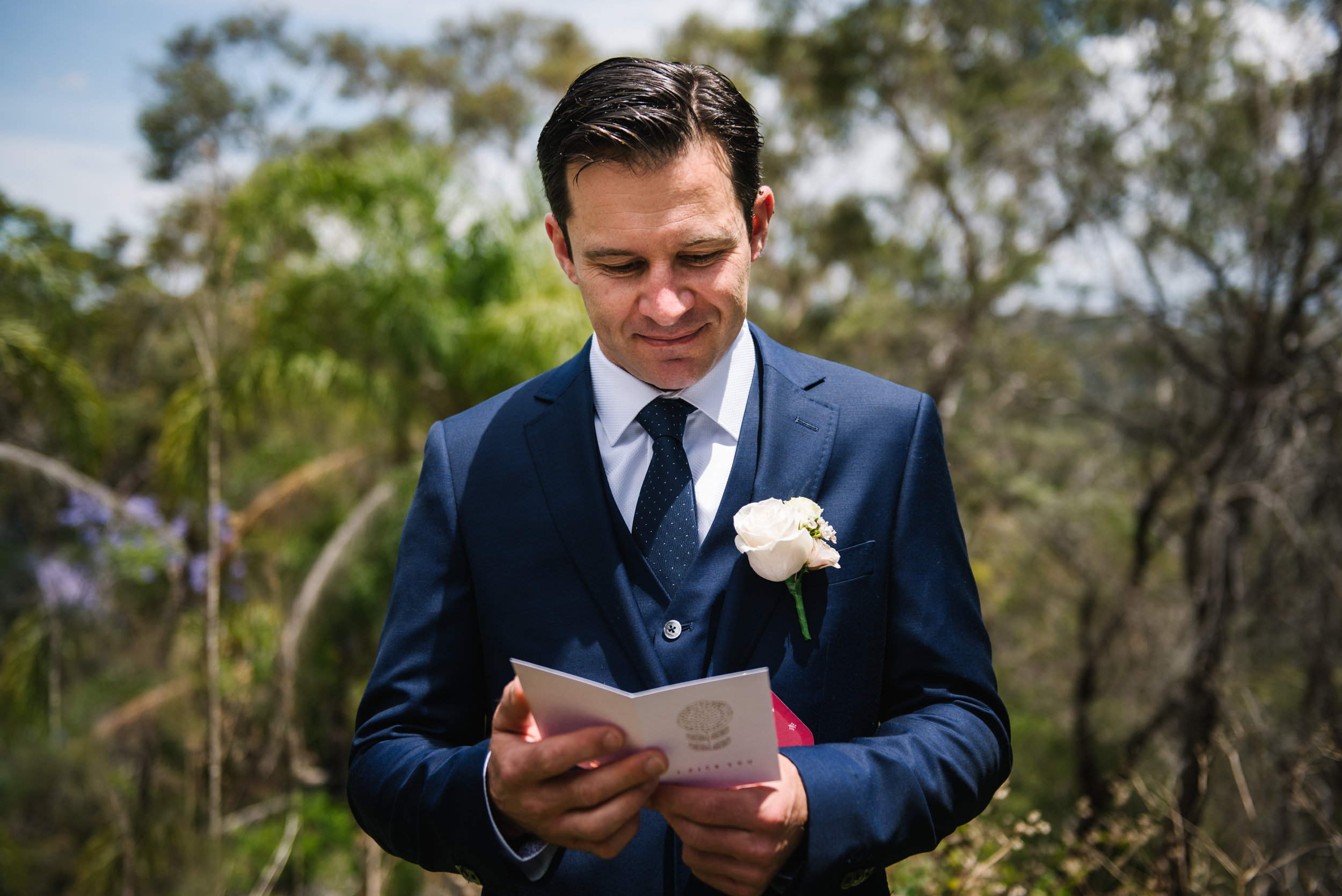 Groom reading card from bride on wedding day