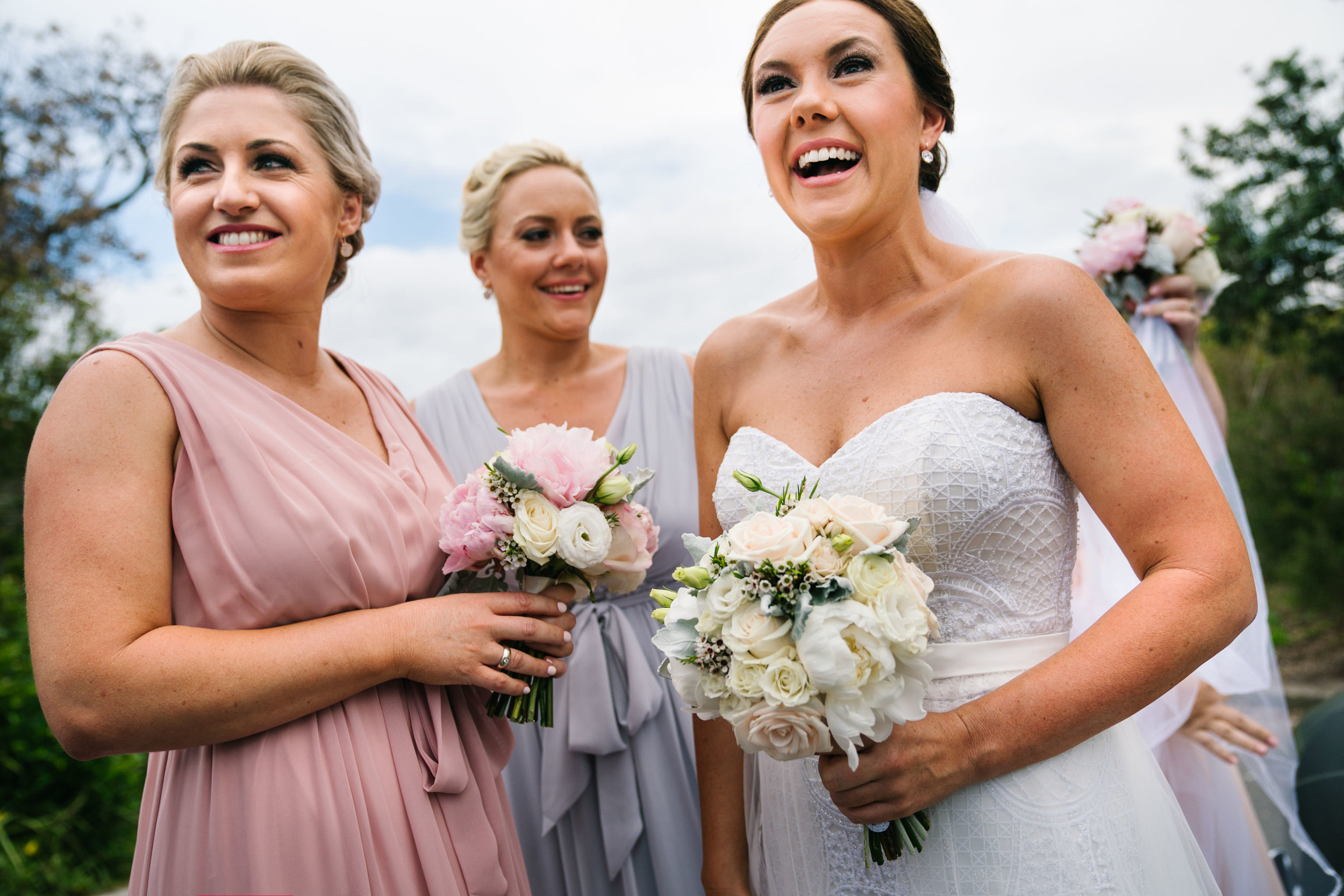 Bride laughing with bridesmaids before wedding ceremony at Shelly Beach