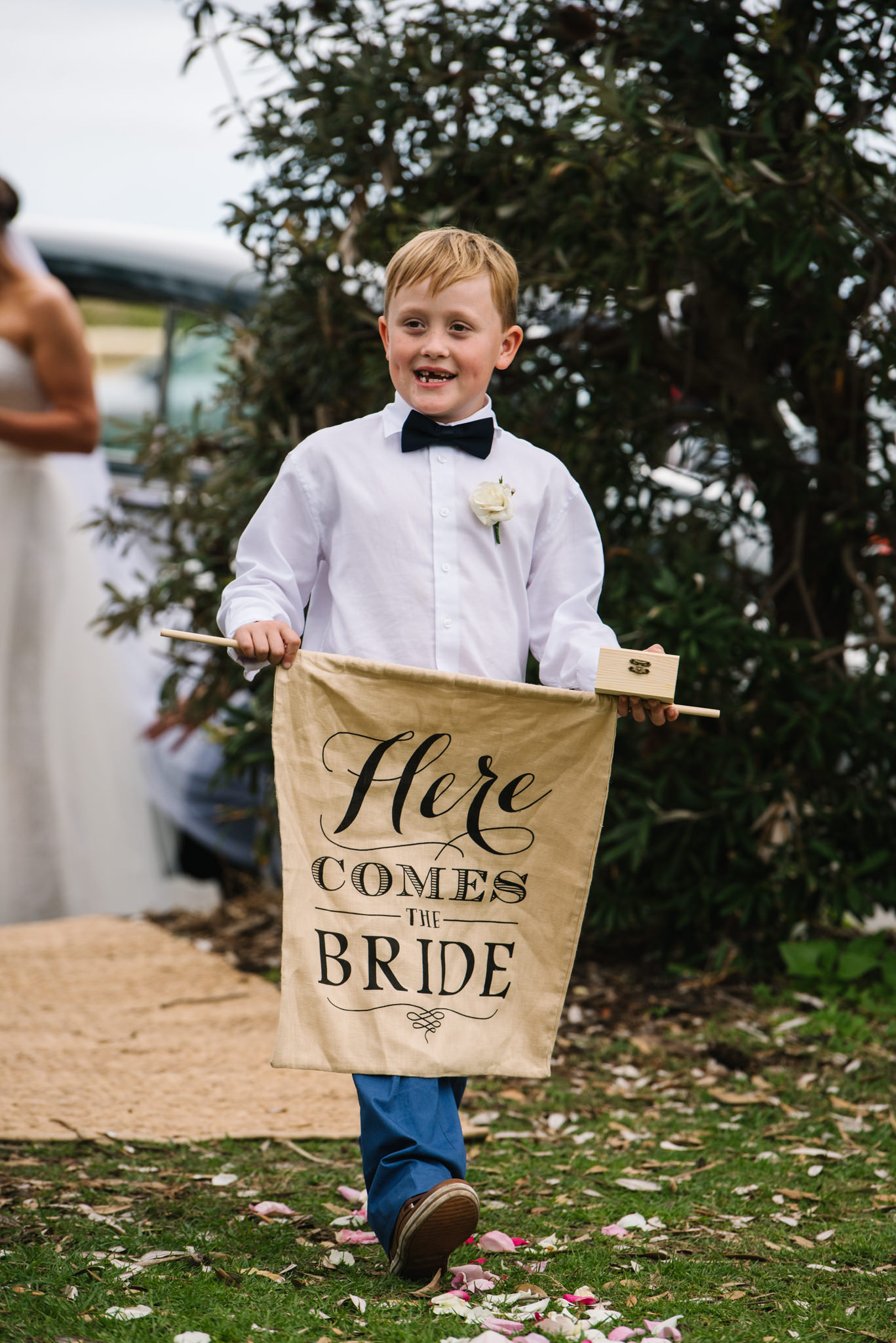 Ring bearer walking down aisle holding Here Comes the Bride sign