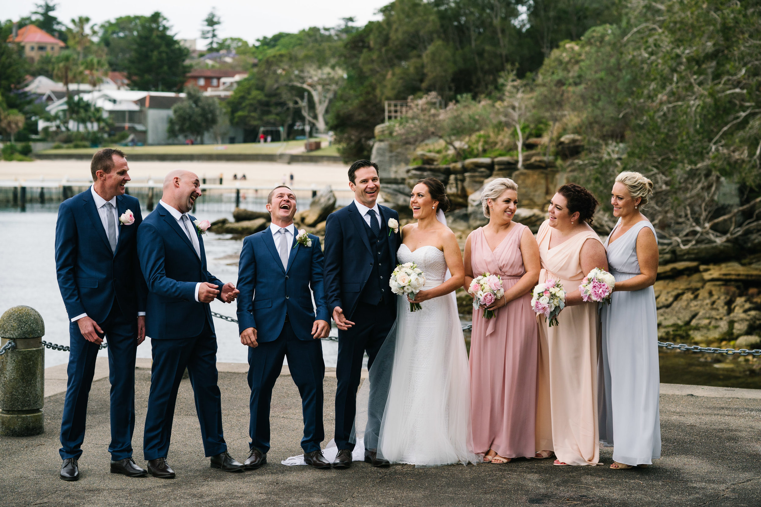 Bridal party laughing with Little Manly Beach in the backdrop