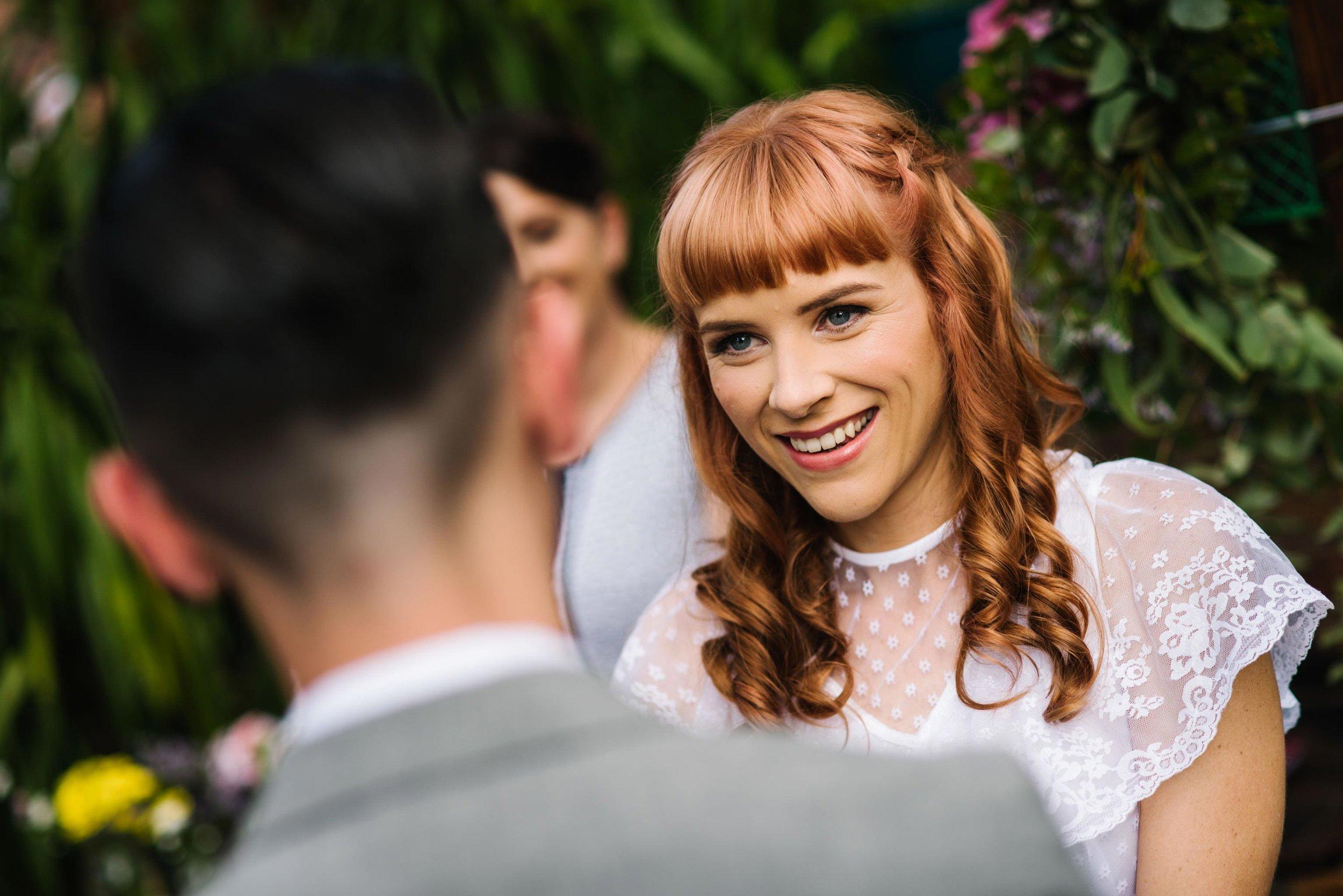 Bride smiles at groom during garden wedding ceremony in Sydney