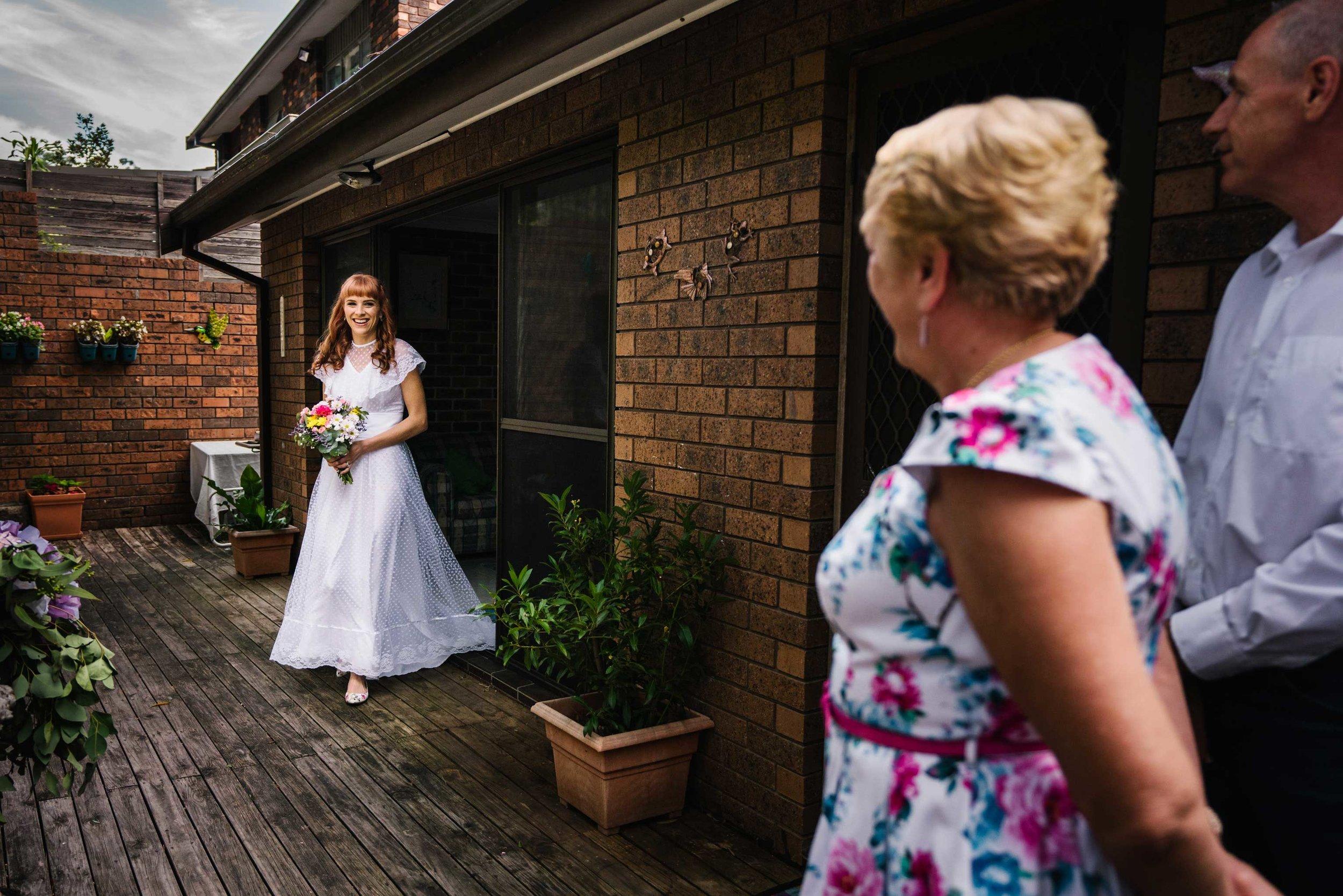 Bride in vintage wedding gown enters garden ceremony