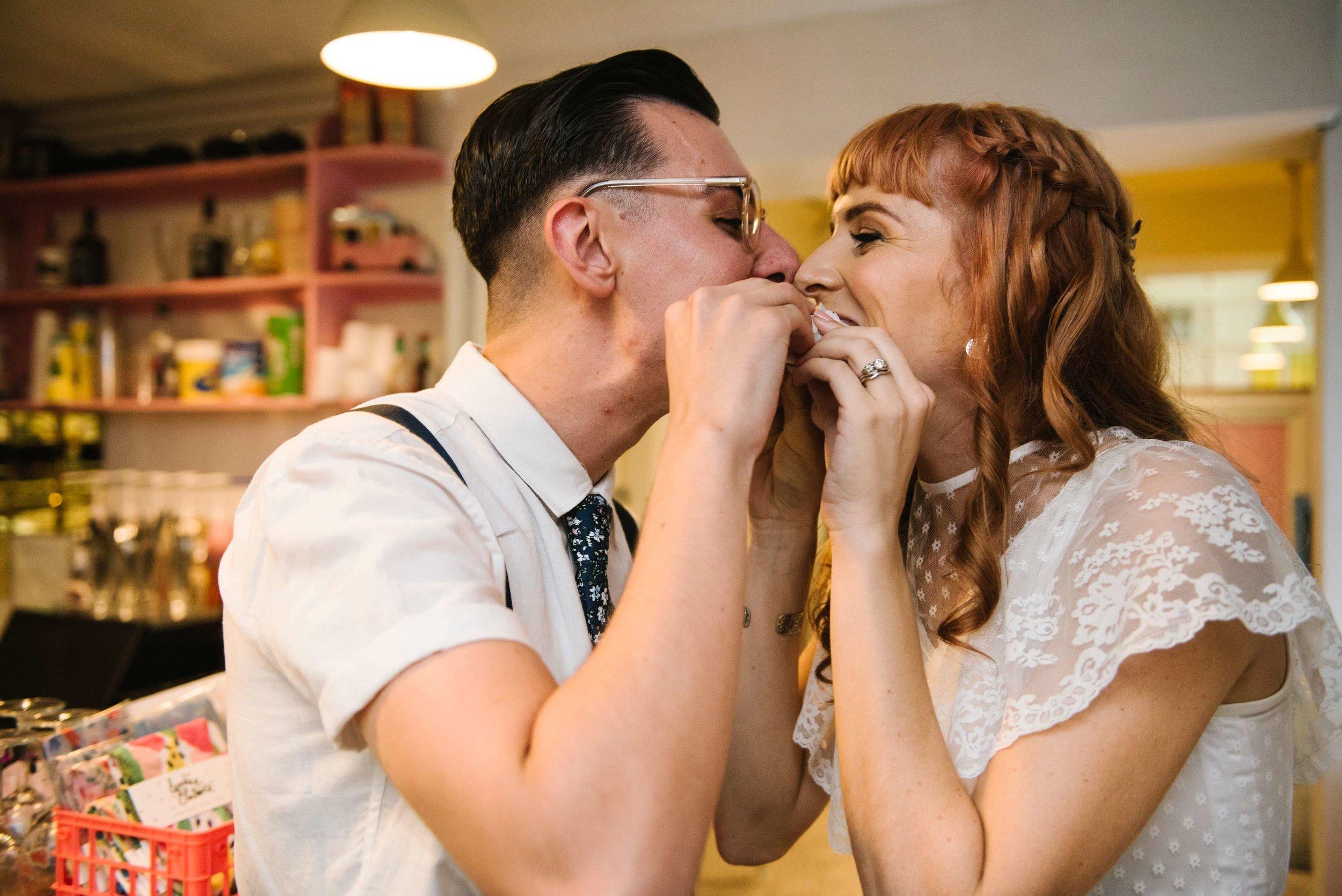 Newlyweds eating donut wedding cake