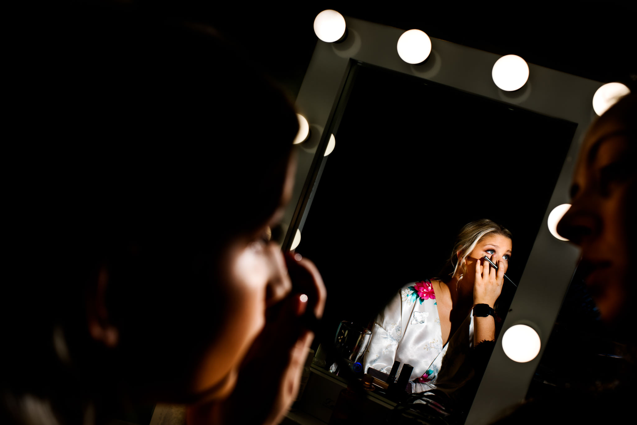 View of bride in mirror getting makeup done before wedding