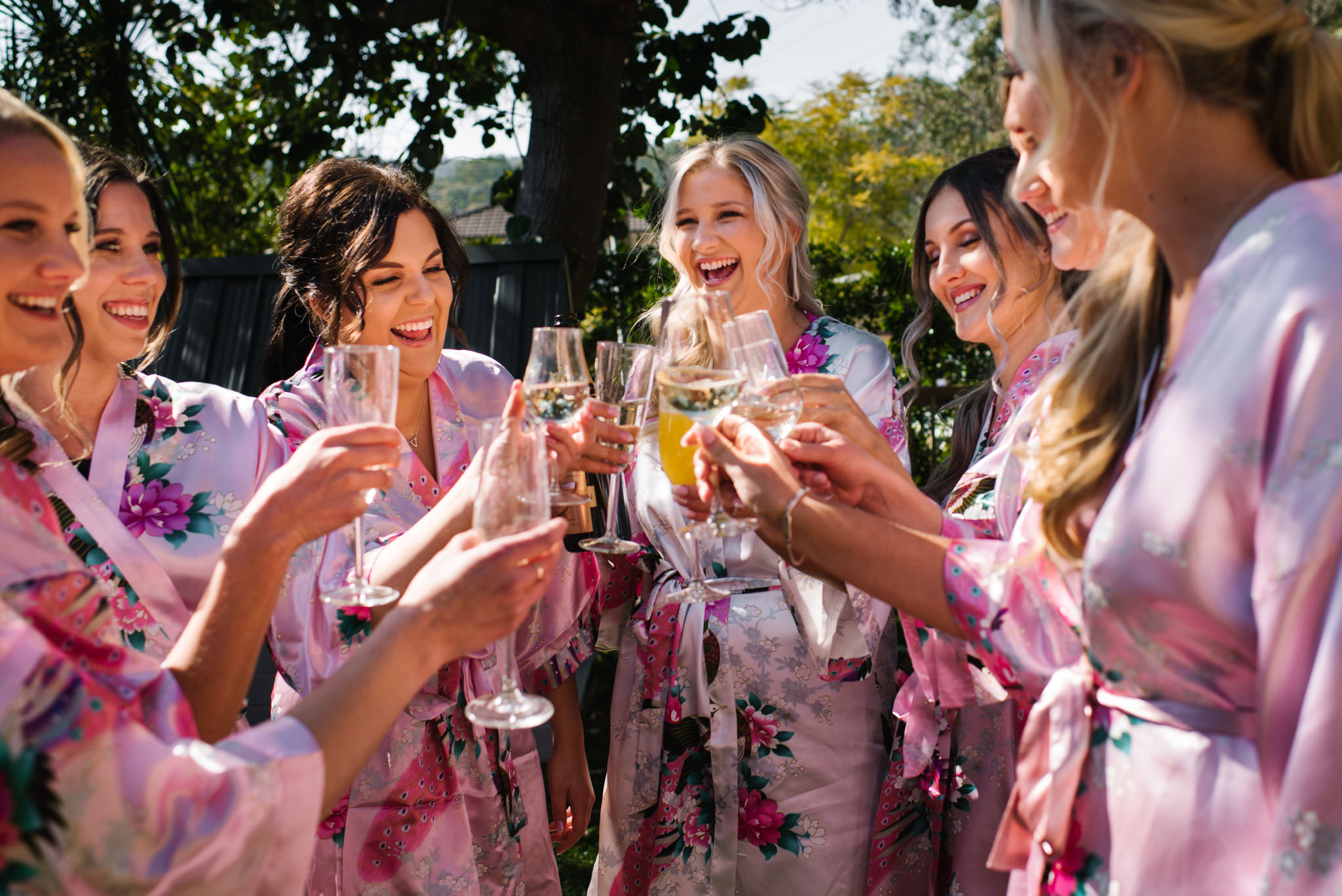 Bride and bridesmaids in pink floral dressing gowns cheers with champagne