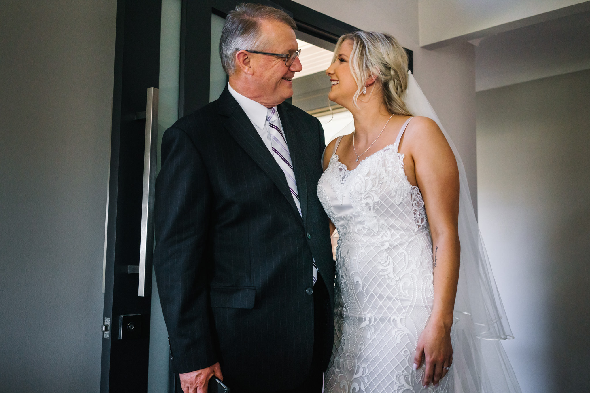 Bride and father hugging and smiling in family home