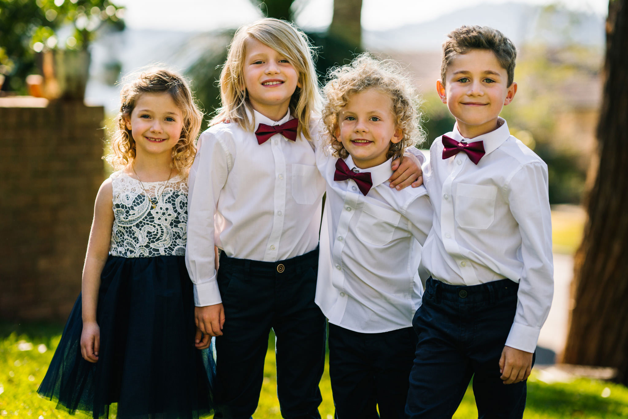 Flower girl and pageboys in bowties smiling