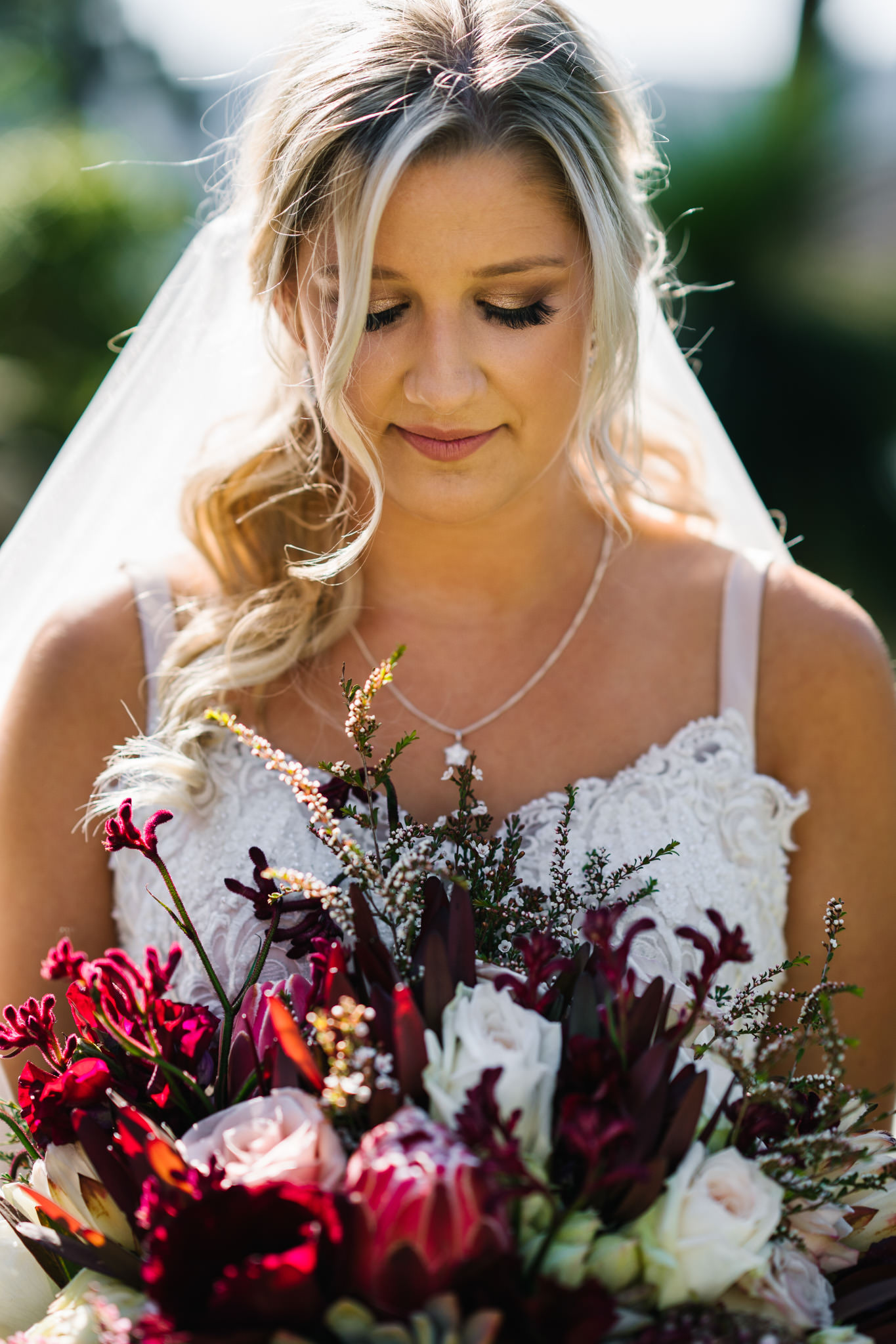 Bride holding bouquet with proteas, roses and kangaroo paw
