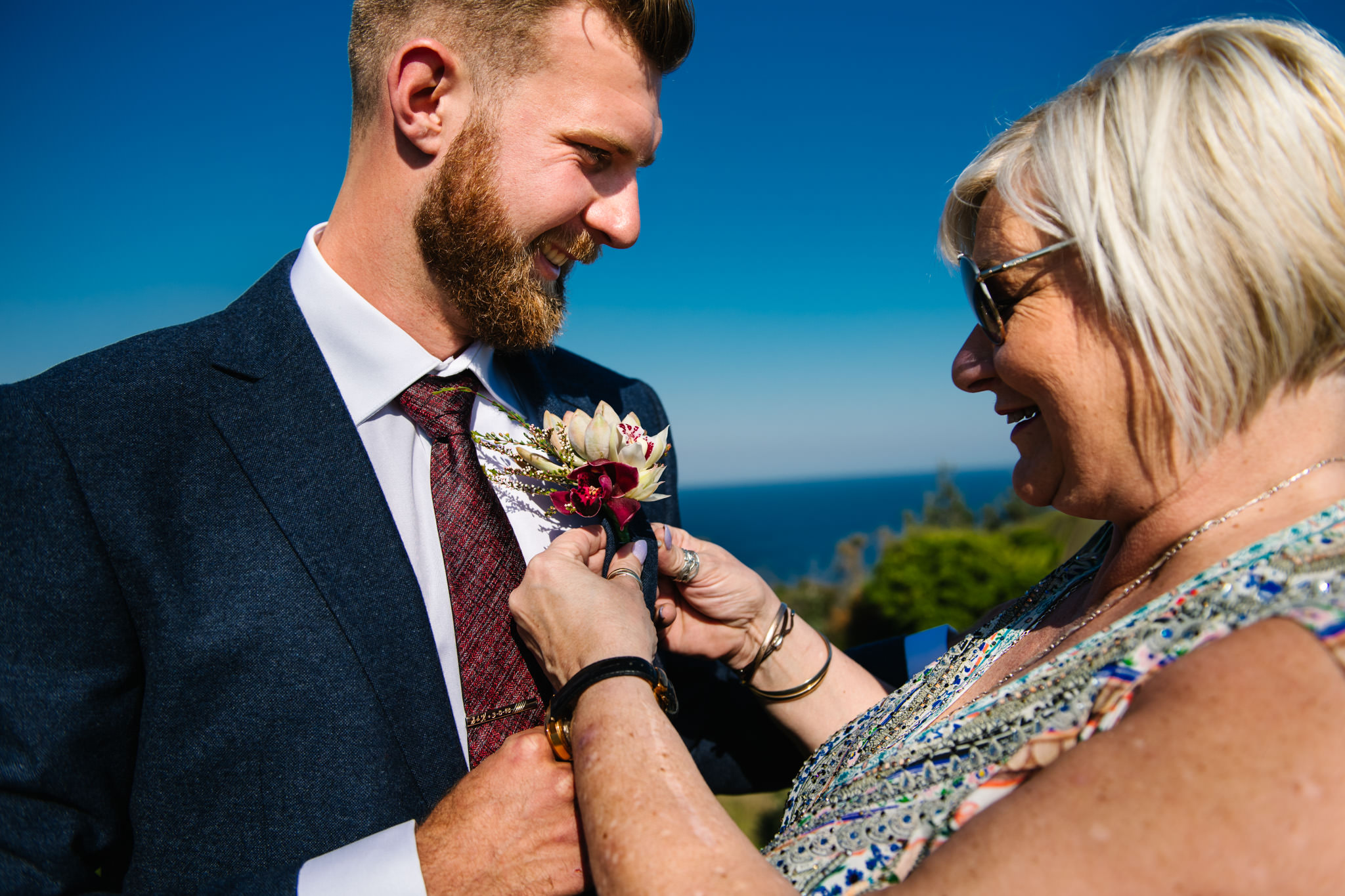 Groom's mother attaching his buttonhole with the beach in the background