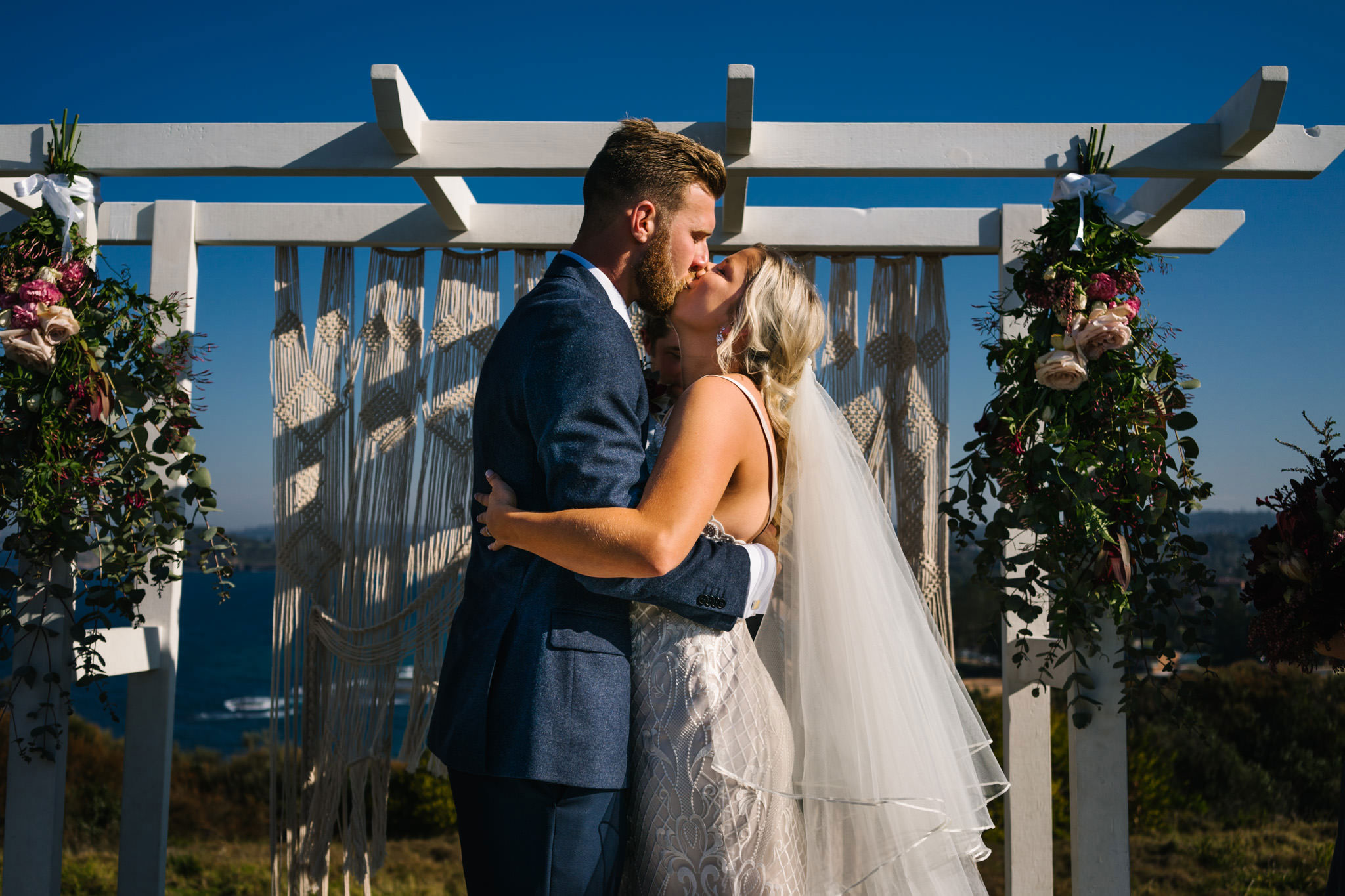 Newlyweds first kiss under boho wedding altar at outdoor headland ceremony