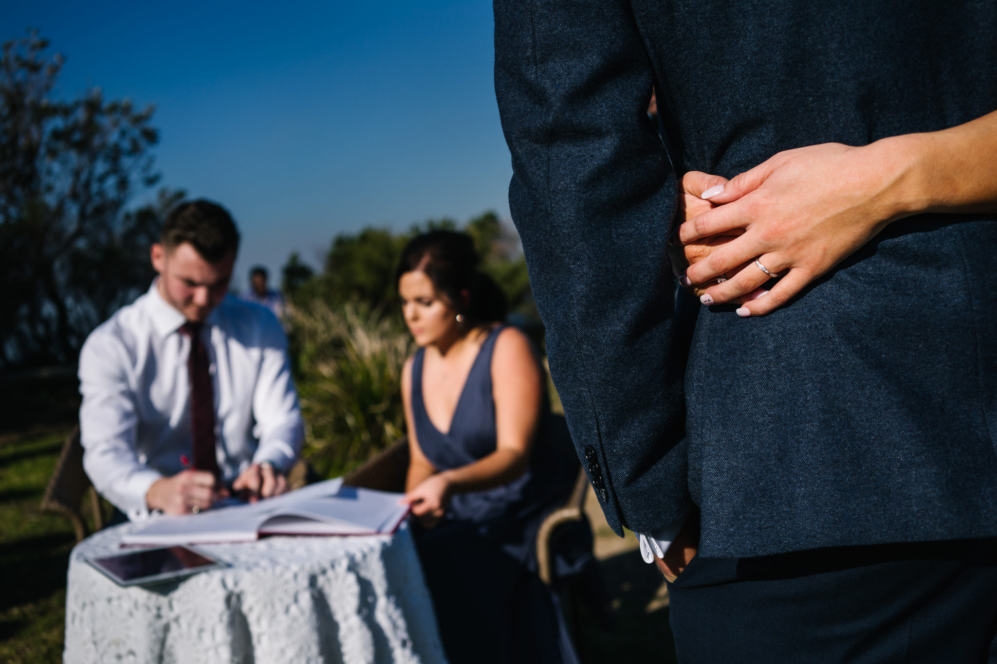 Bride and groom embrace during document signing