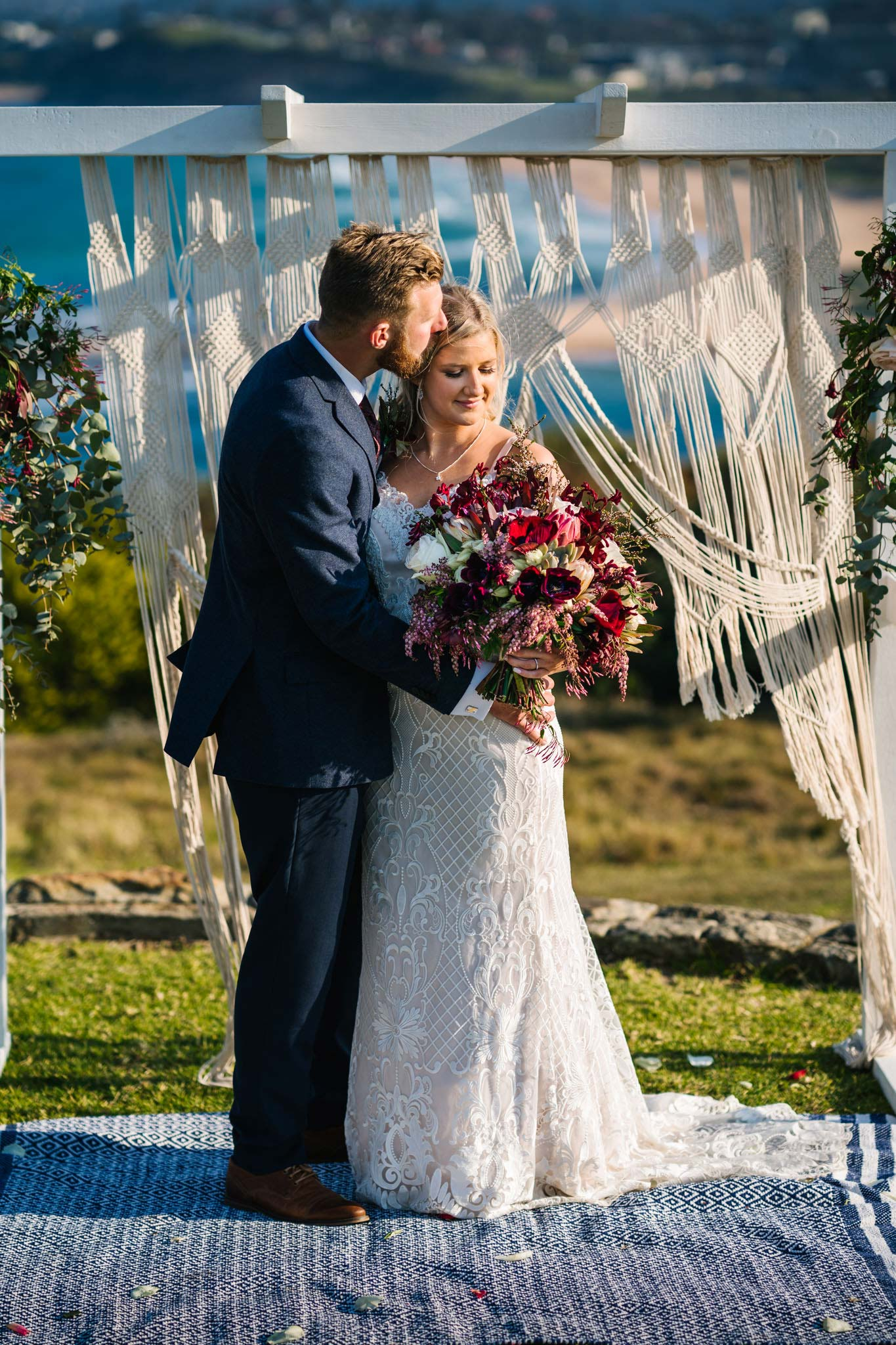 Newlyweds pose in front of their macrame boho wedding altar on Mona Vale headland