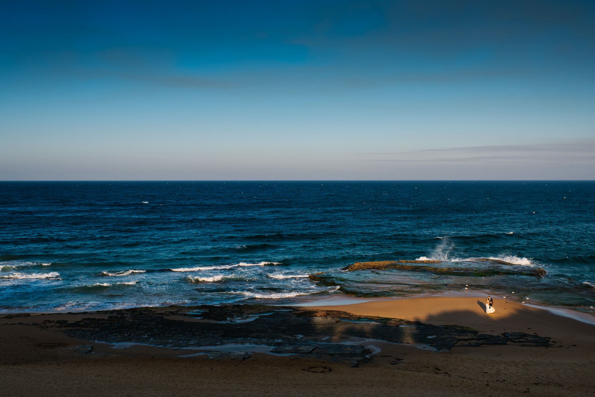 View of bride and groom on Turimetta beach