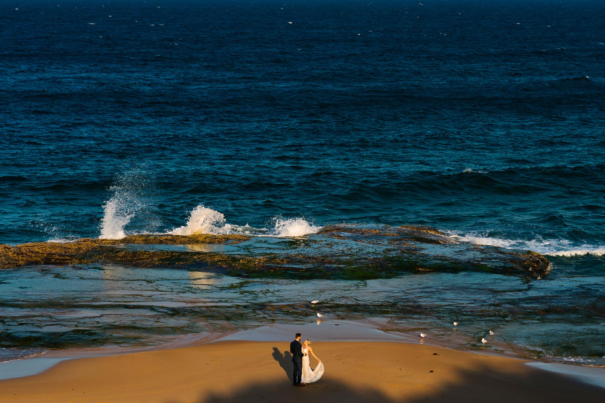 Bride and groom embracing on Turimetta beach in the Northern Beaches of Sydney