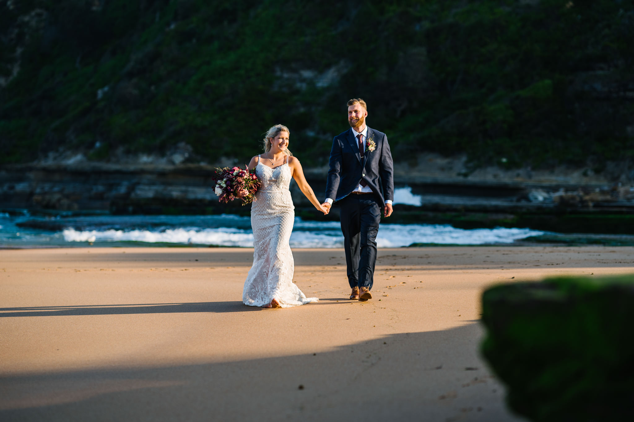 Bride and groom walking up the beach after Northern Beaches wedding