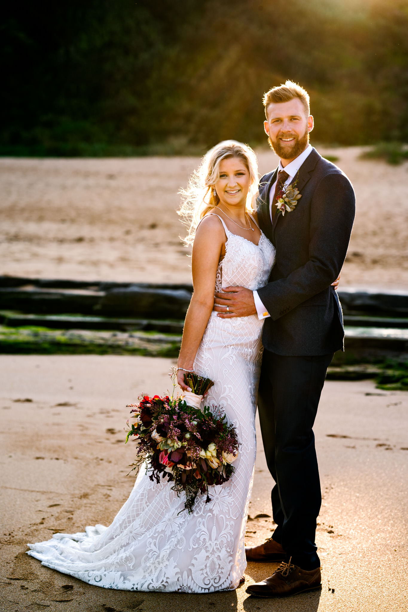 Young bride and groom posing on Turimetta beach