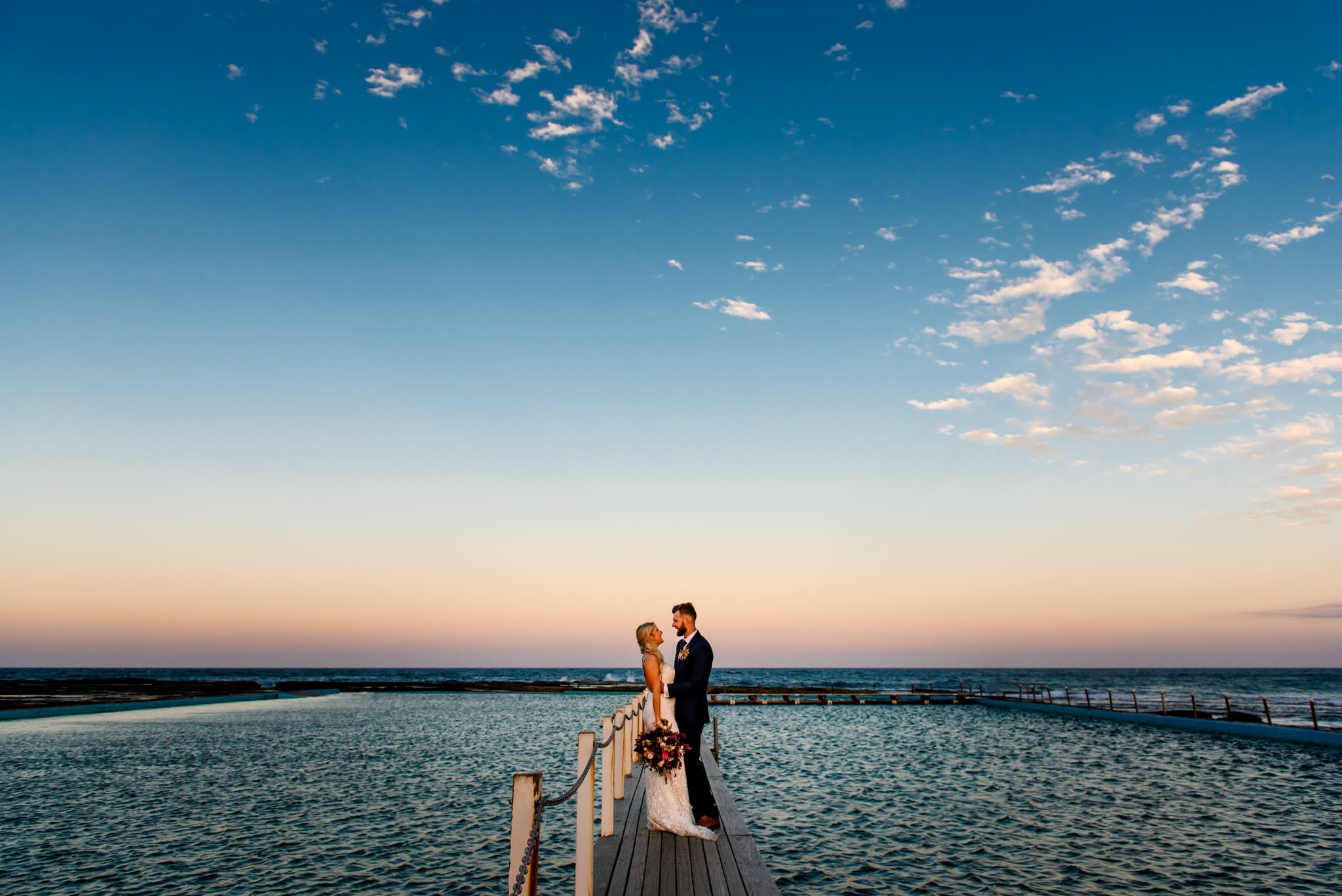 Newlyweds on dock at Narrabeen ocean pool at sunset