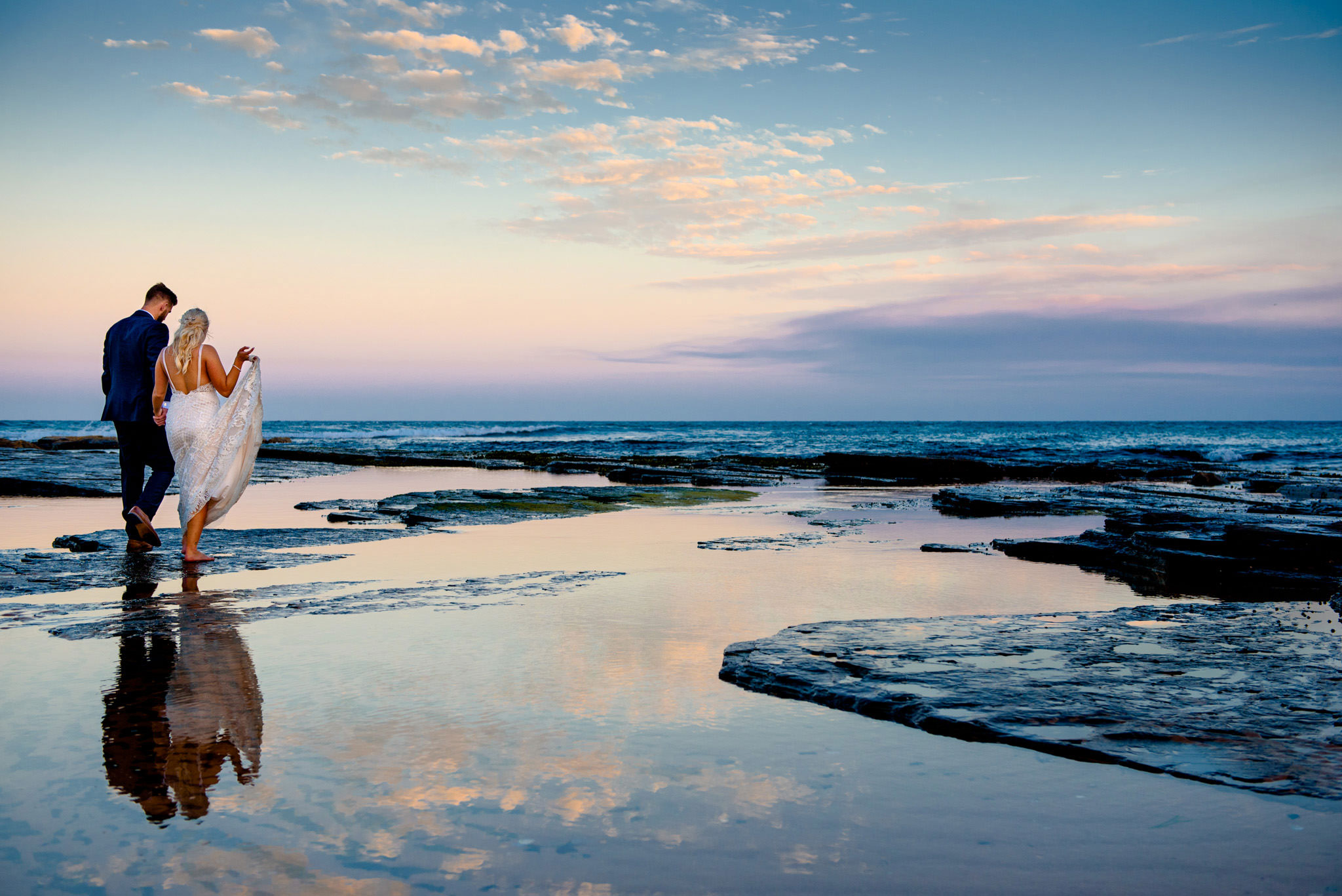 Reflection of bride and groom in water at Narrabeen beach