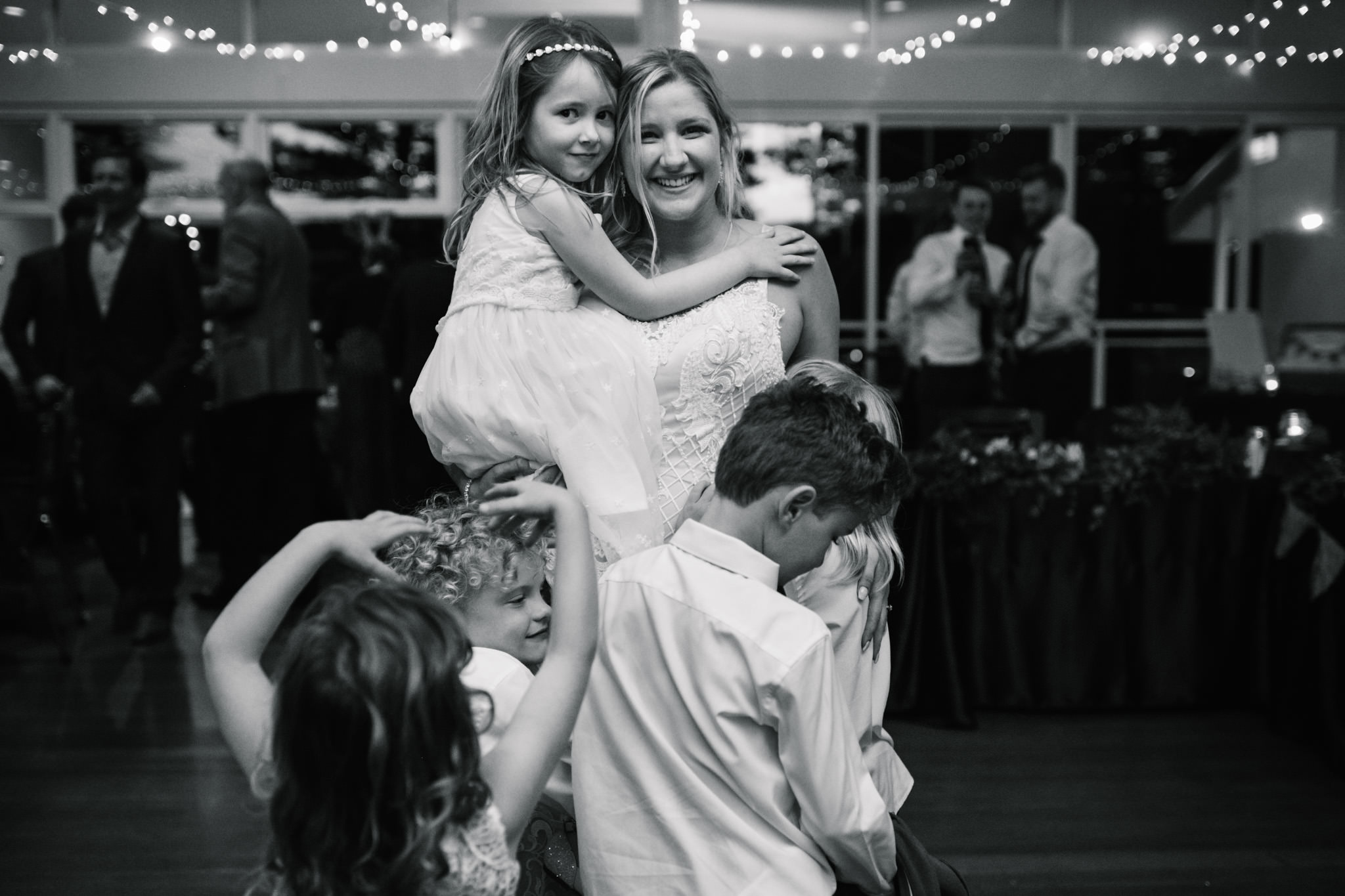 Bride being embraced by all the children attending her wedding