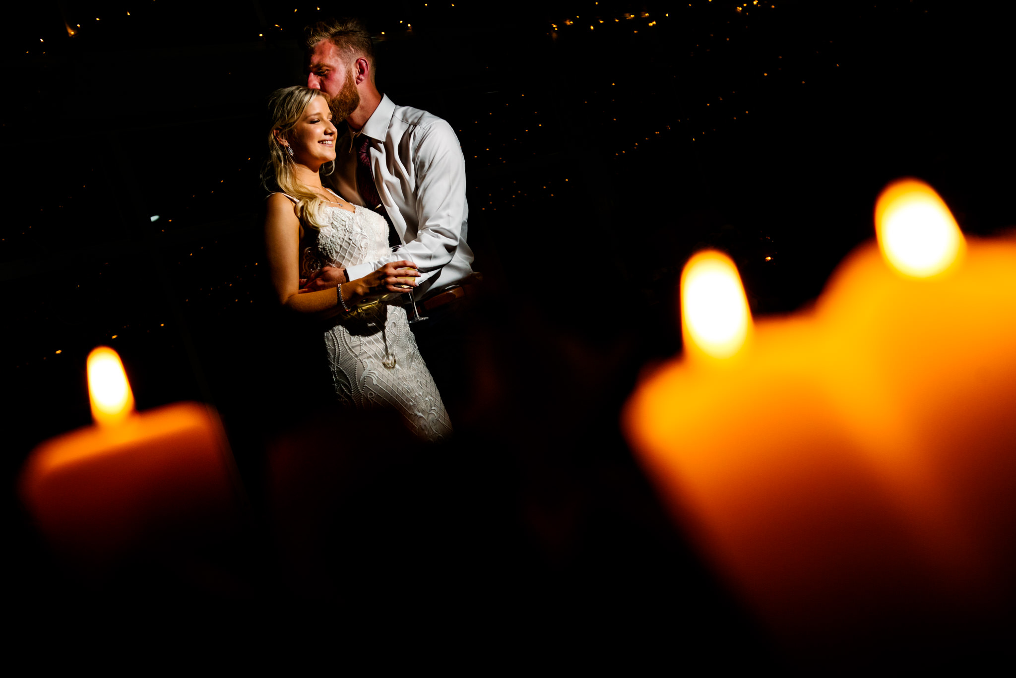 Portrait of newlyweds with candlelight in the foreground at Narrabeen Beach SLSC