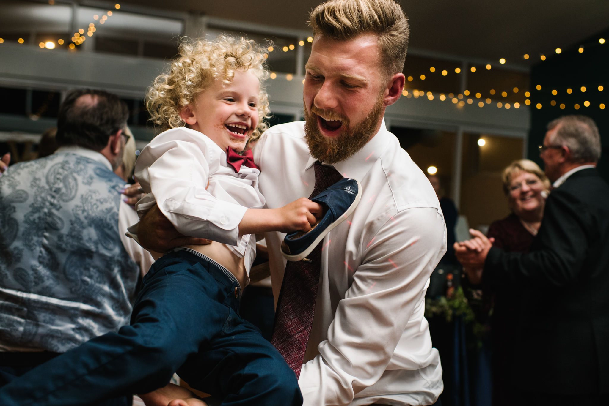 Groom playing with ring bearer both laughing