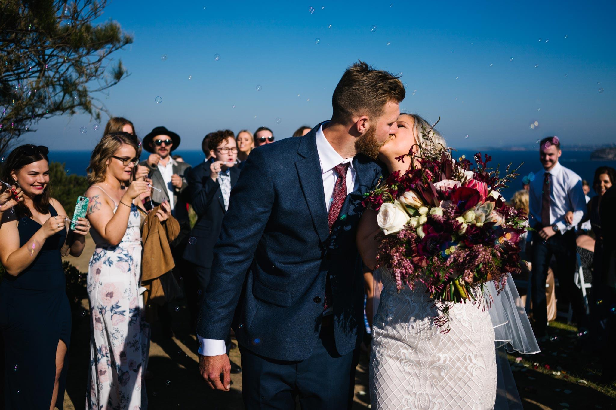 Newlyweds kissing after Mona Vale headland wedding ceremony