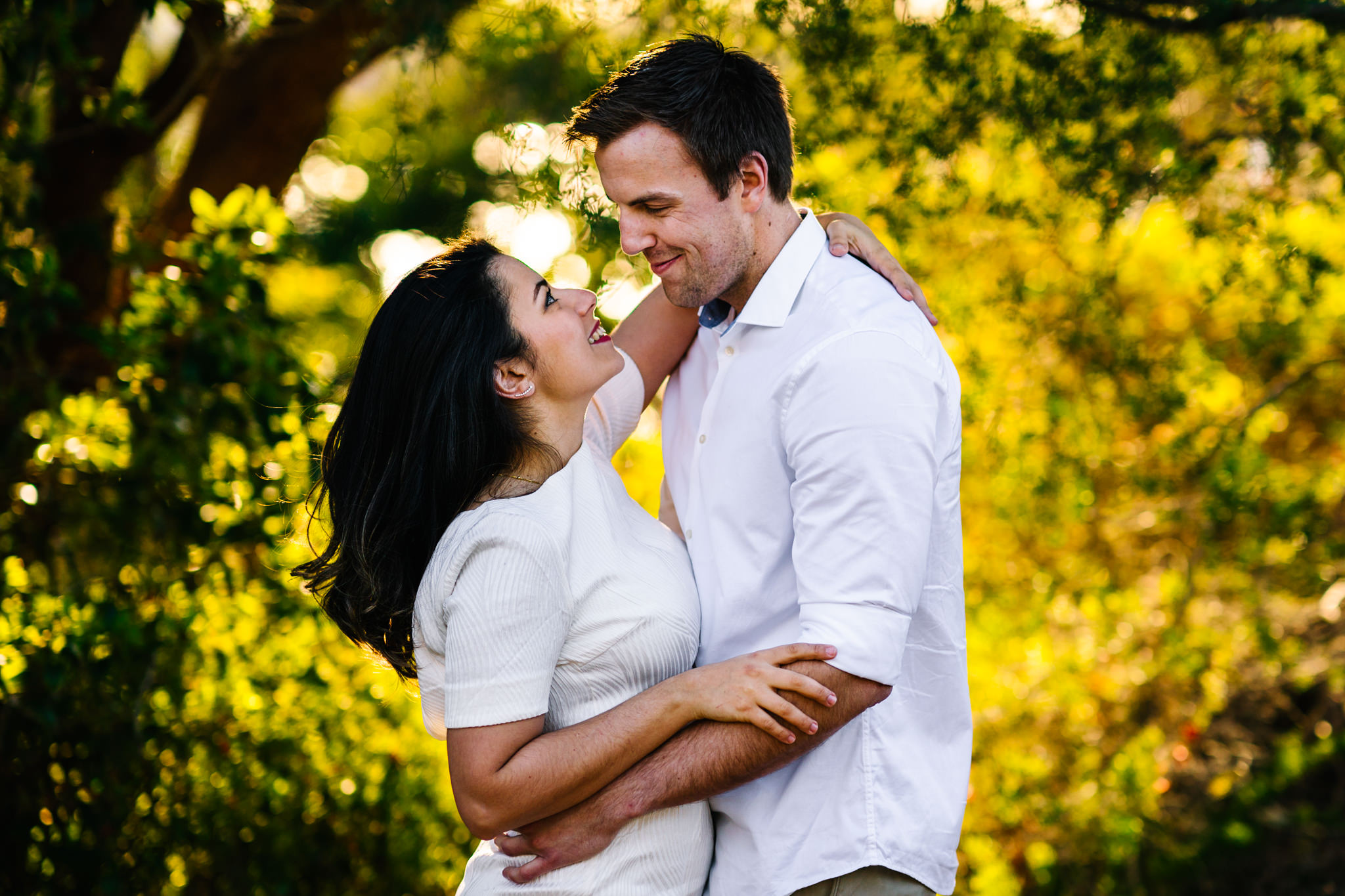 Engaged couple smile lovingly at each other during Sydney engagement session