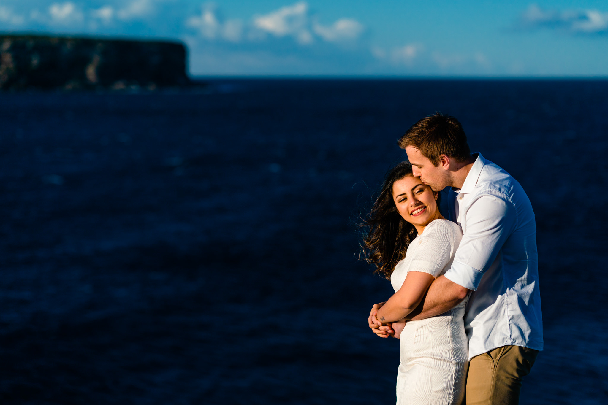 Couple embrace with views of the Sydney harbour in the background